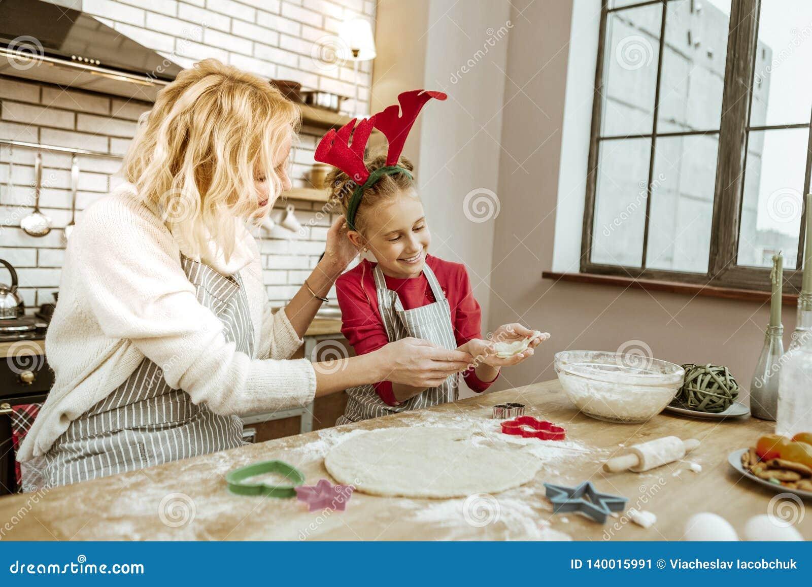 Mulher loura de irradiação que elogia sua filha pequena para o bom trabalho