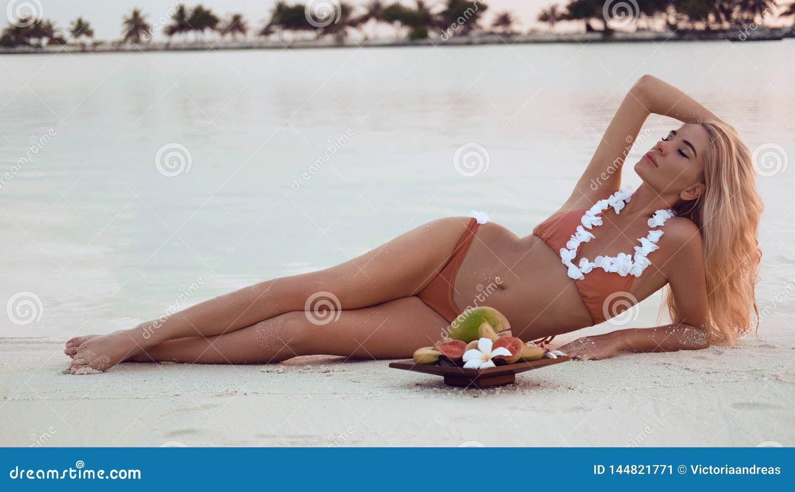 Mulher loura despreocupada que encontra-se na areia branca que aprecia o por do sol bonito na praia tropical Modelo  sexy  do biq