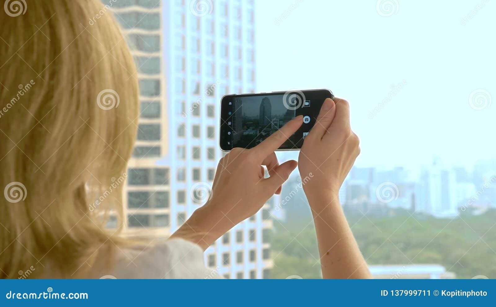 Mulher loura elegante que faz uma foto no telefone fotografias da mulher a vista da janela dos arranha-céus