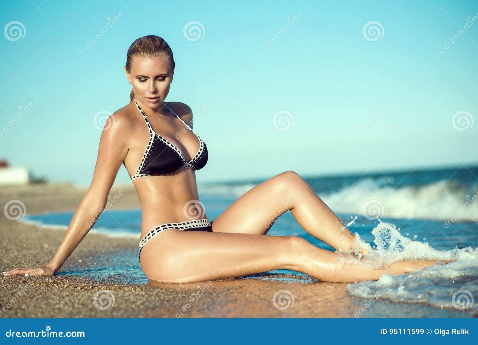A mulher loura glam suntanned bonita com pele molhada e o cabelo que sentam-se na praia e que apreciam, seus pés longos lavou pel