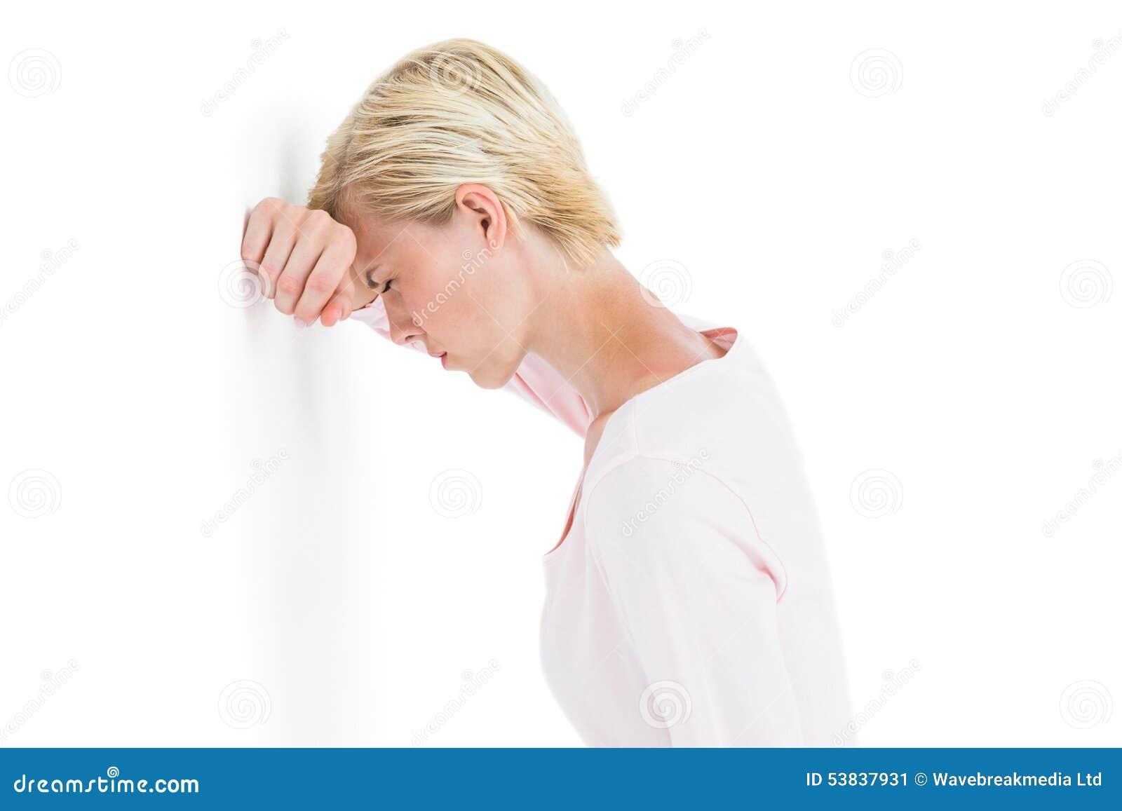 Mulher loura nervosa que inclina-se contra a parede