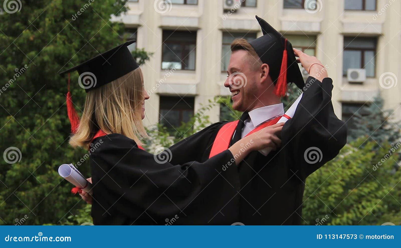 Mulher loura no vestido da graduação que abraça o melhor amigo após ter recebido o diploma vídeos de arquivo