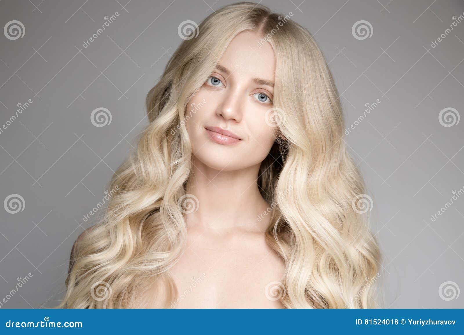 Mulher loura nova bonita com cabelo ondulado longo