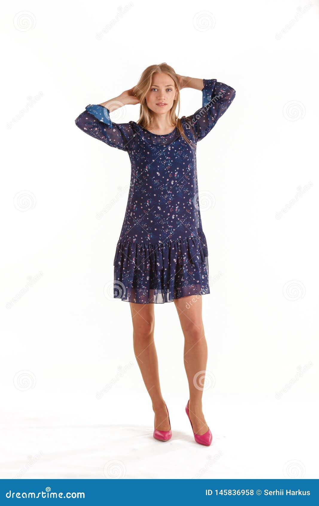 Mulher loura nova bonita em escuro - vestido azul com a c?pia floral isolada no fundo branco
