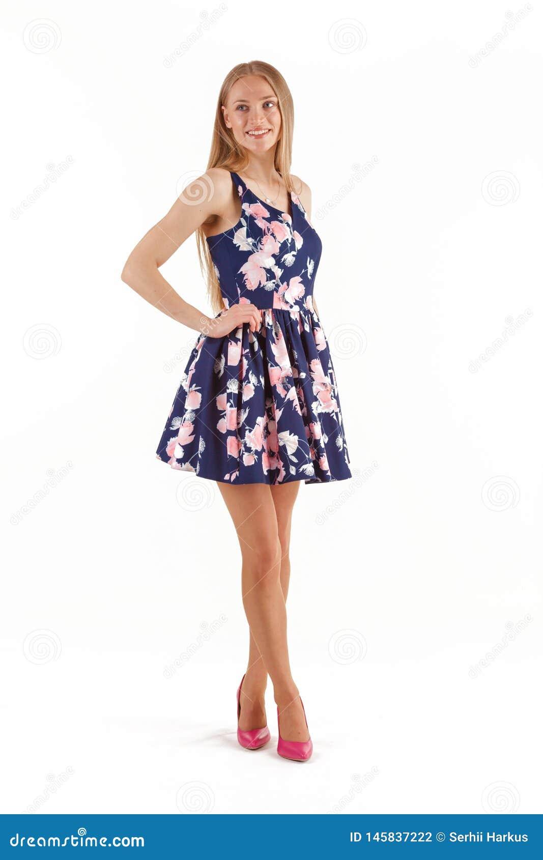 Mulher loura nova bonita no vestido azul com o bordado floral isolado no fundo branco