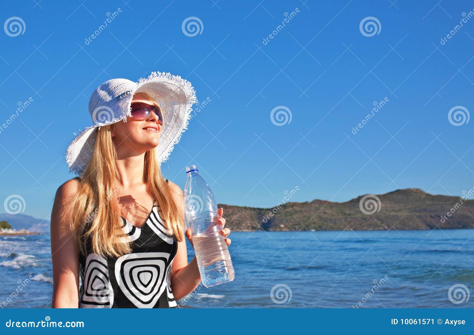Mulher loura nova com o frasco da água