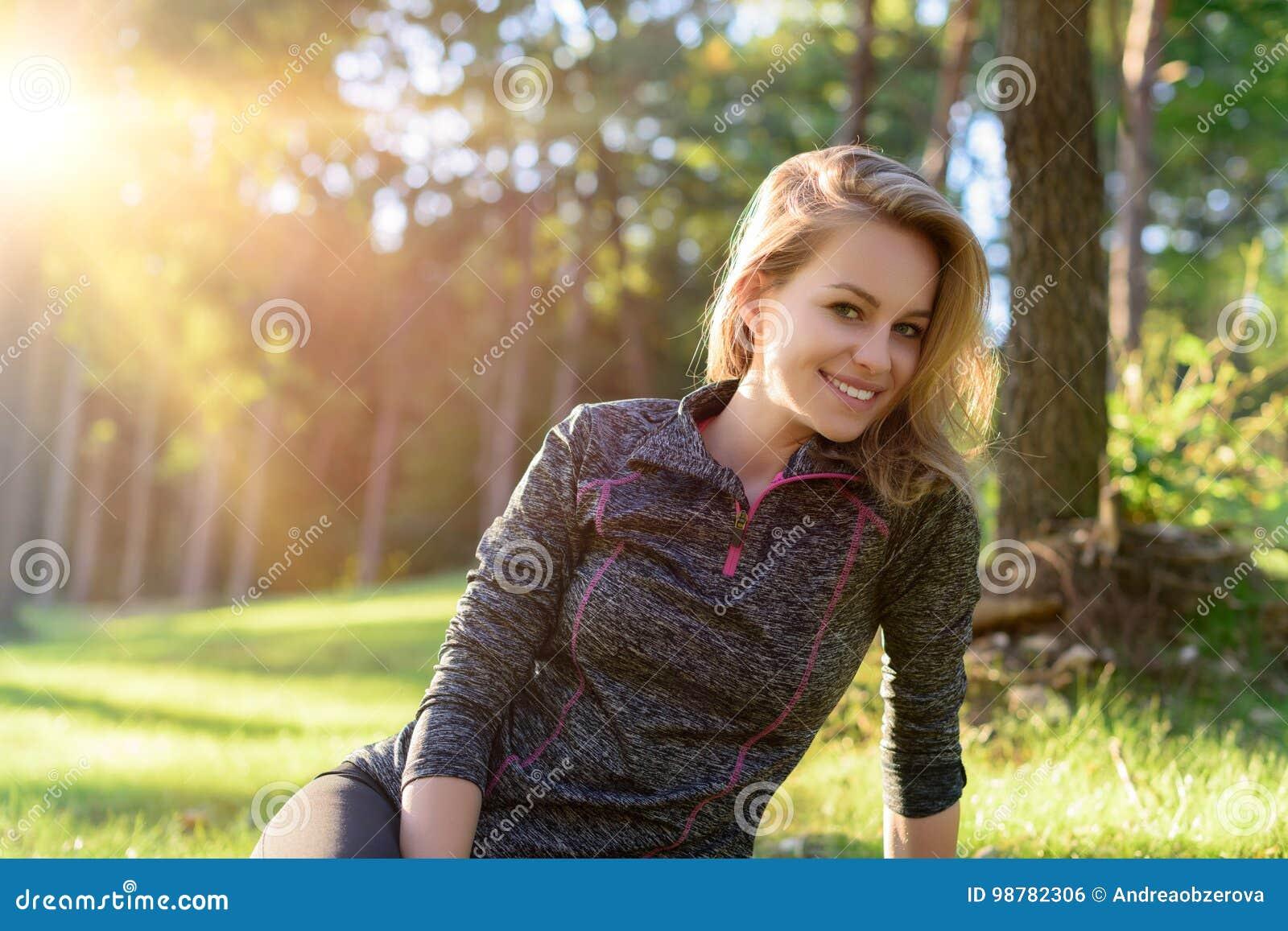 Mulher loura nova de sorriso atrativa no sportswear, relaxando após o exercício