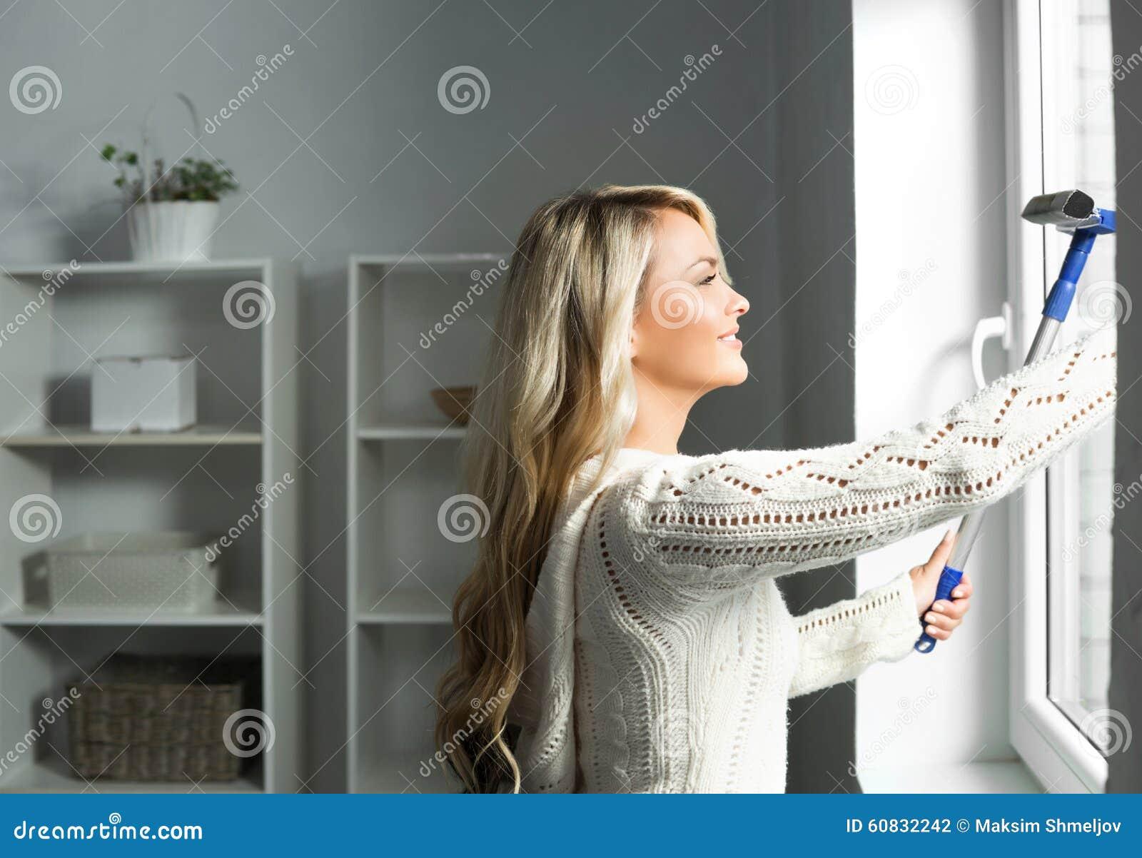 Mulher loura nova e bonita que limpa a janela