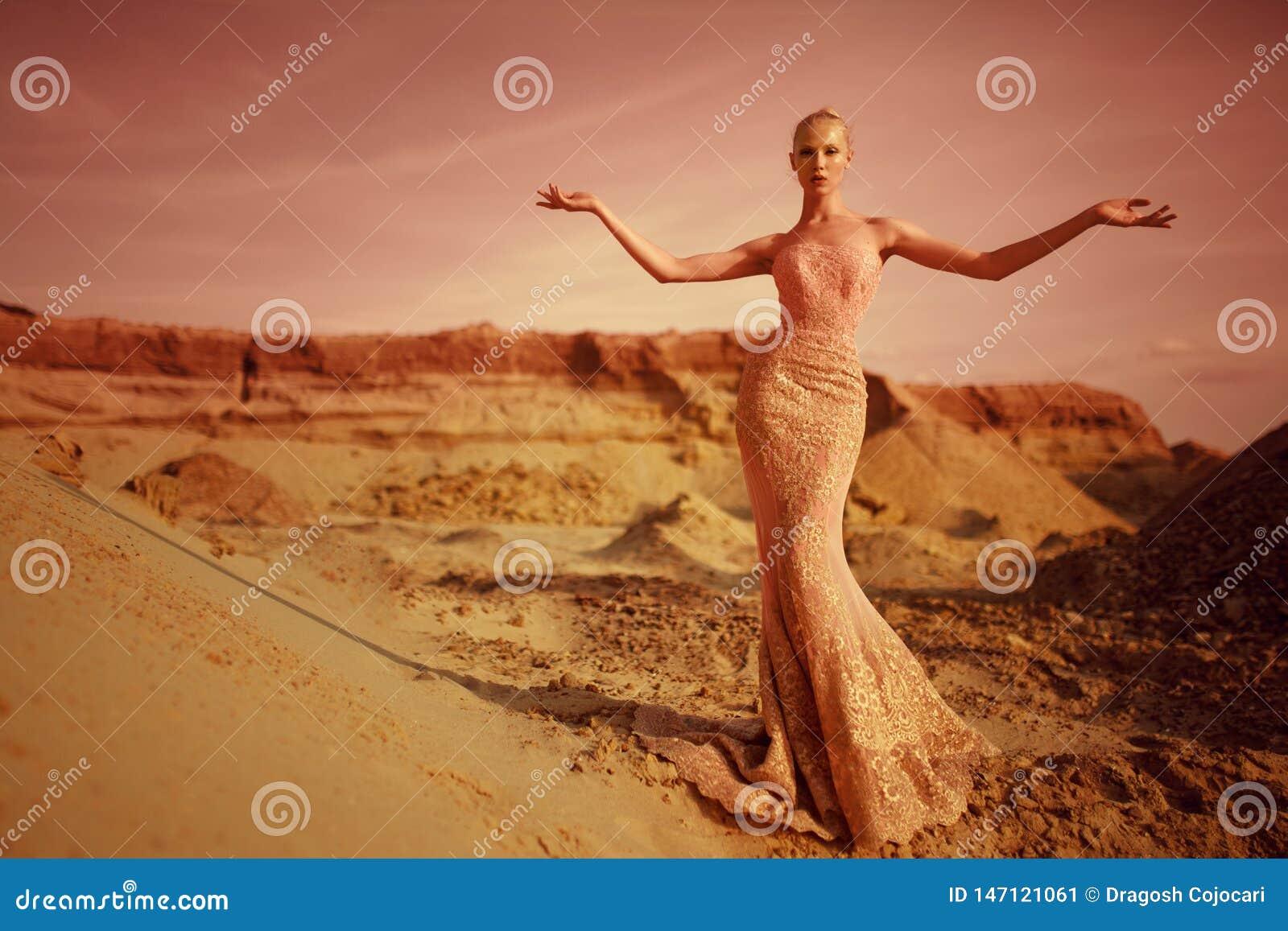 Mulher loura nova elegante no deserto no suporte longo do vestido do ouro com mãos abertas, durante no fundo do por do sol