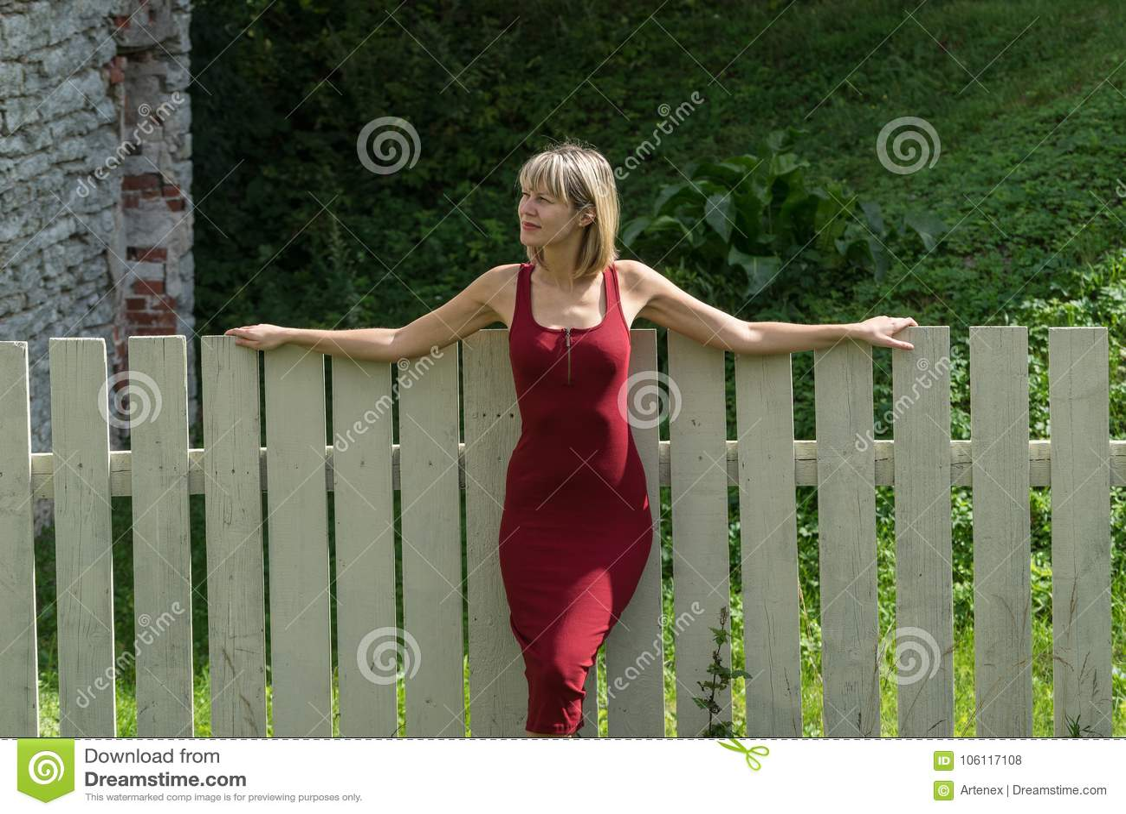 Mulher loura nova em um vestido vermelho que inclina-se contra a cerca de madeira