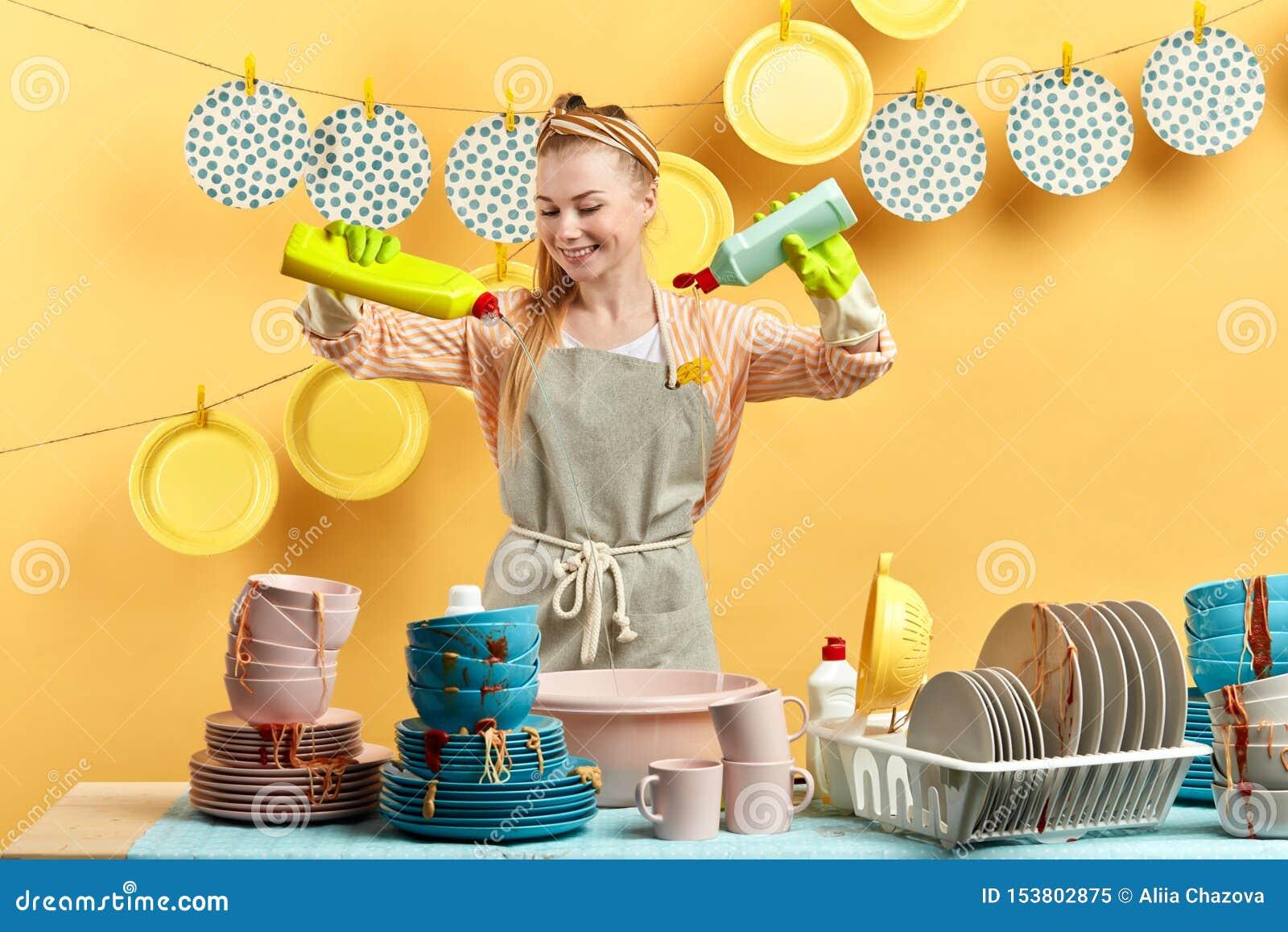 Mulher loura nova feliz entusiasmado que faz trabalhos domésticos