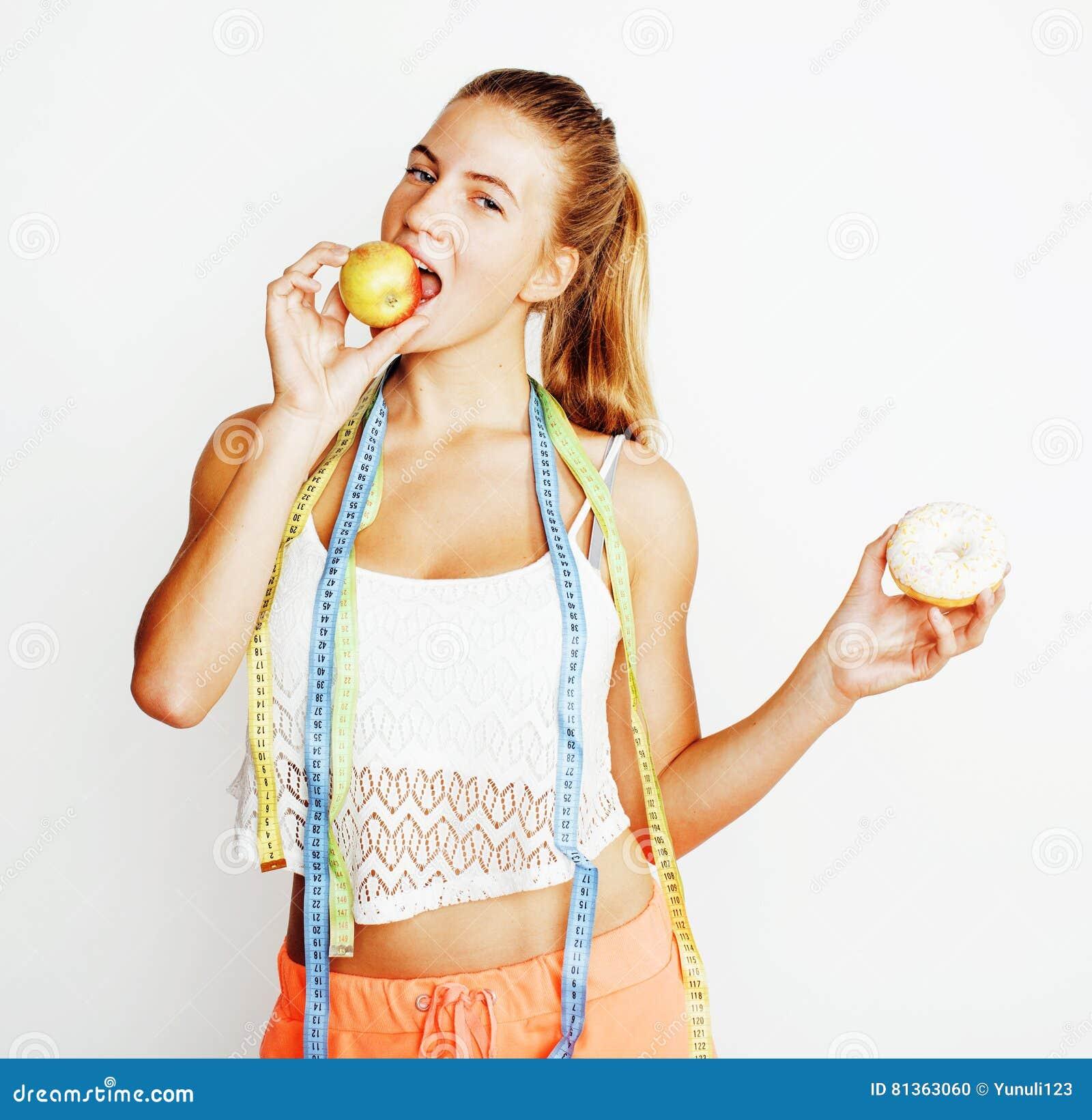 Mulher loura nova que escolhe entre a filhós e o fruto da maçã isolados no fundo branco, conceito dos povos do estilo de vida
