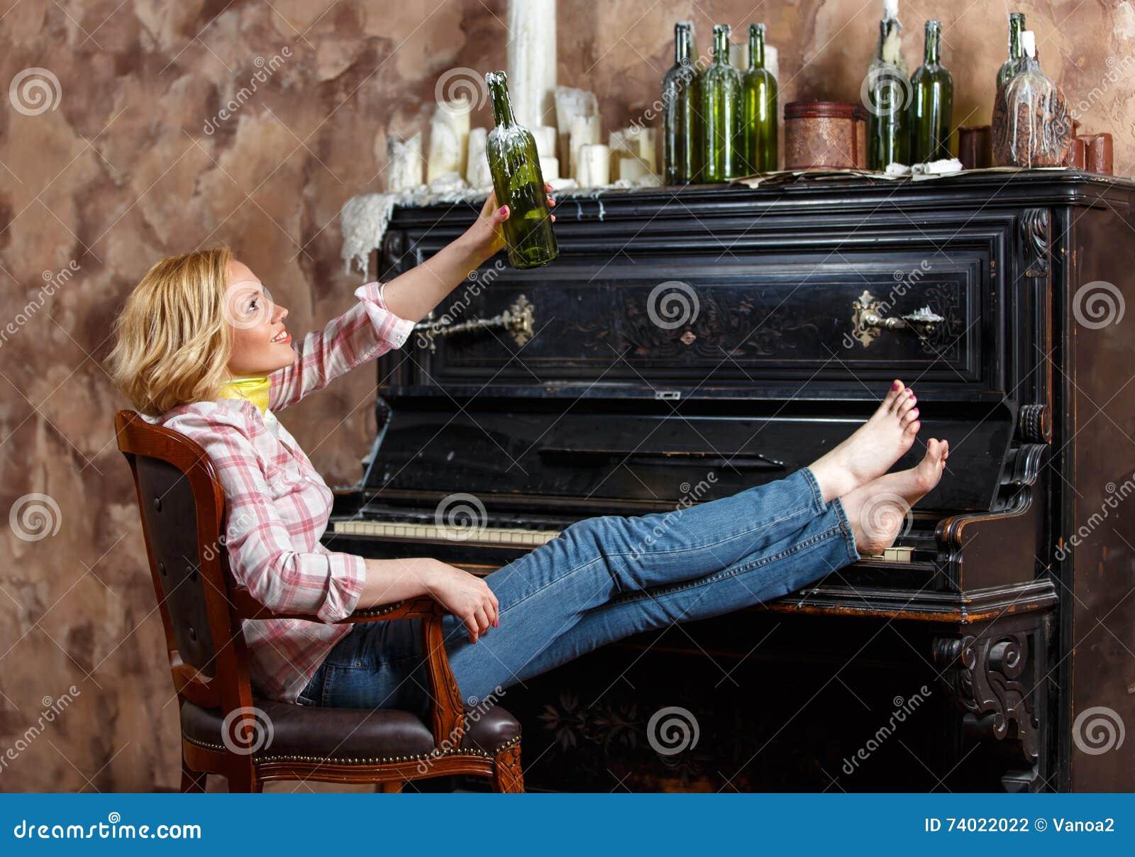 Mulher loura que levanta na poltrona com a garrafa de vinho encerada