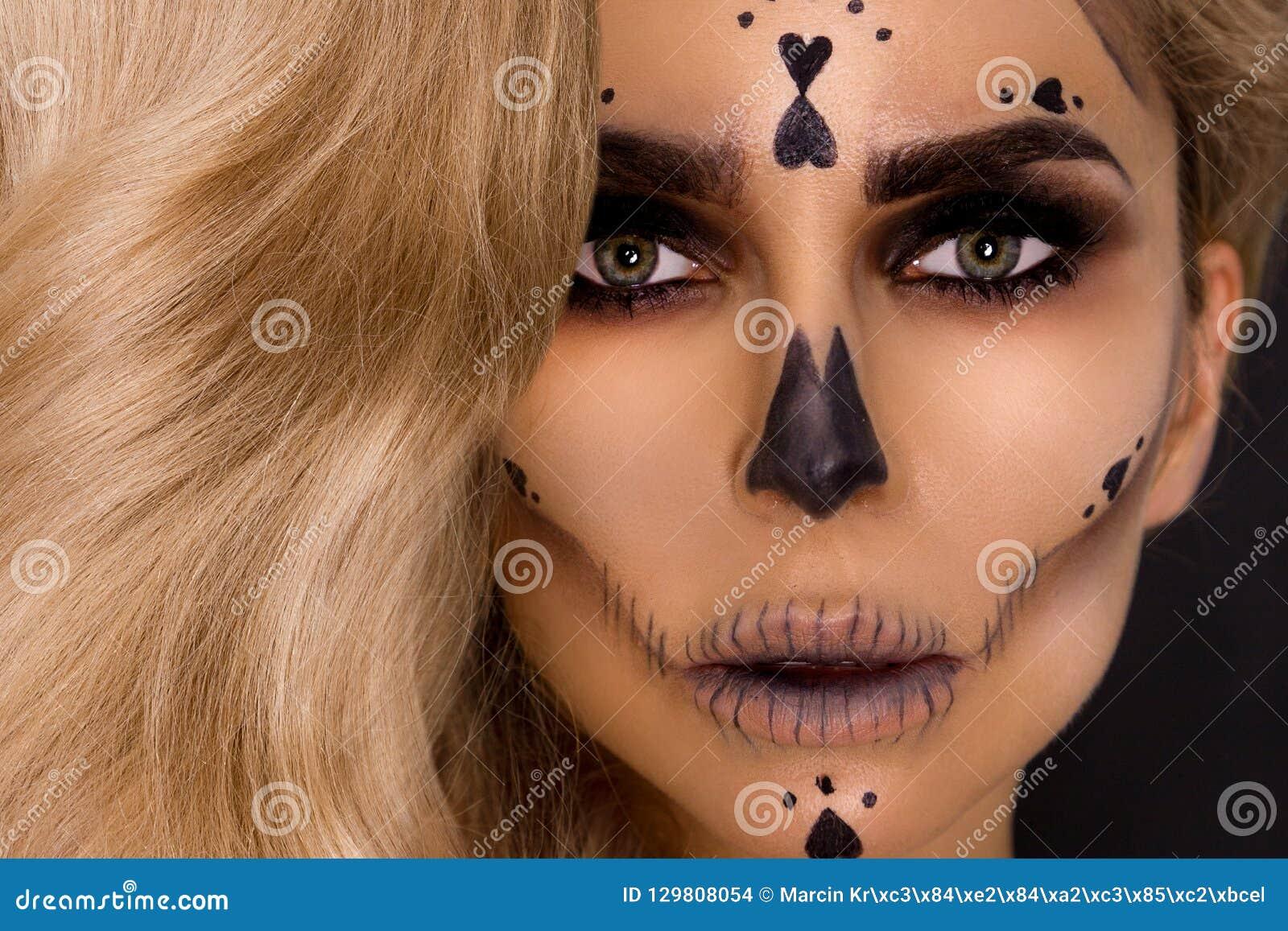 Mulher loura  sexy  na composição de Dia das Bruxas e equipamento de couro em um fundo preto no estúdio Esqueleto, monstro