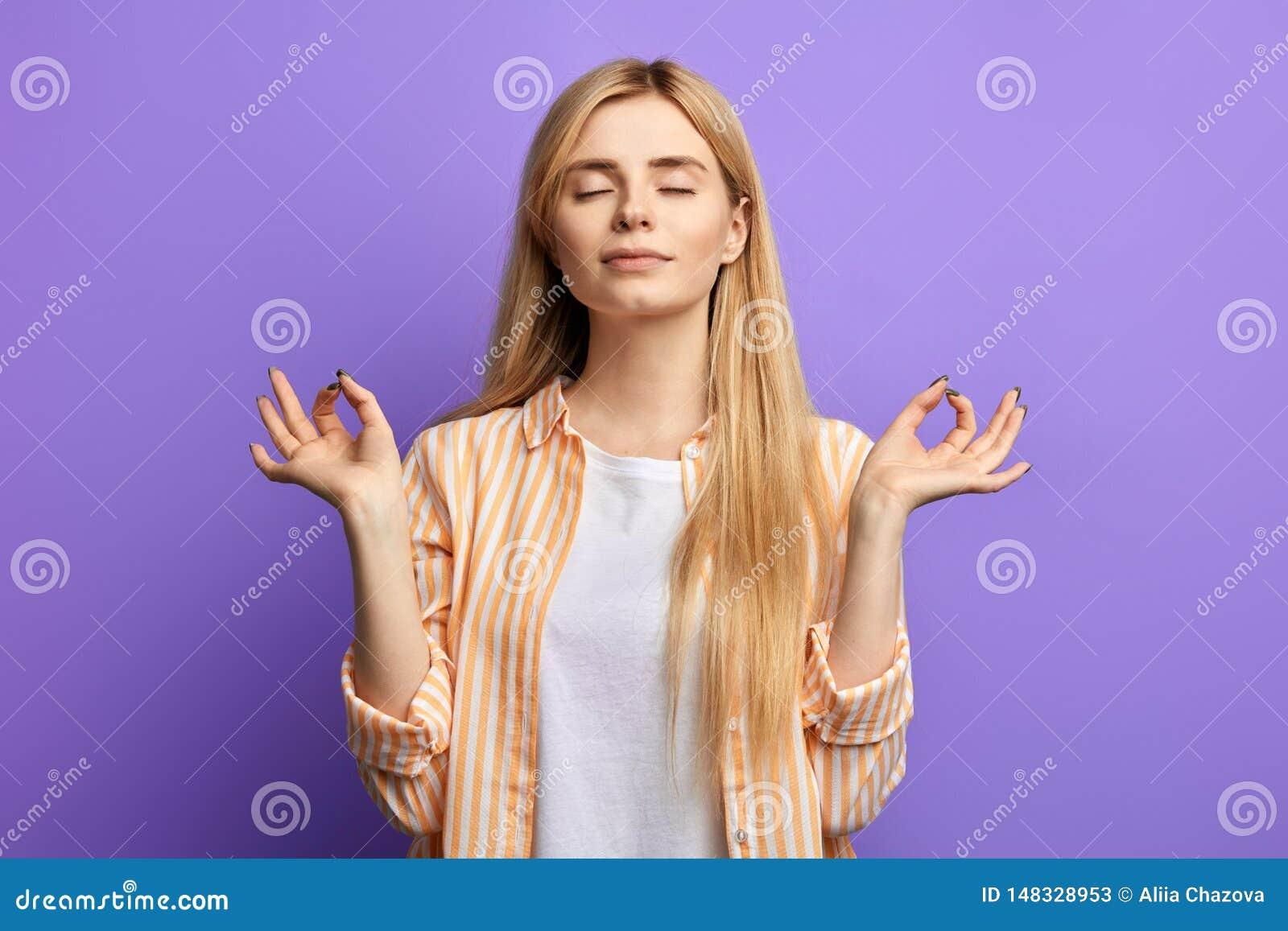 Mulher loura vestida em camisa listrada e no t-shirt branco que fazem a ioga