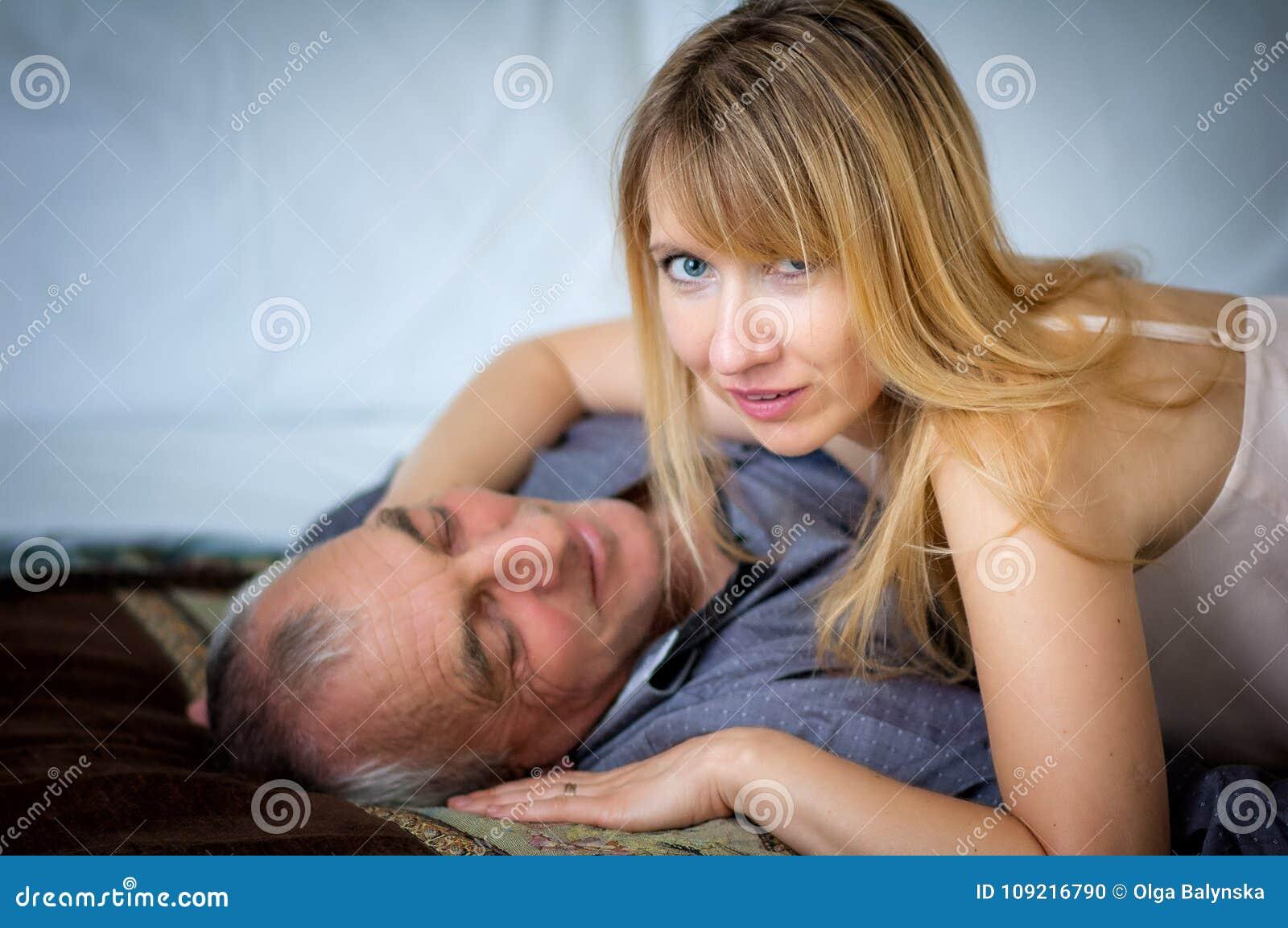 Mulher Louro-de cabelo bonita na roupa interior  sexy  que abraça seu marido superior que encontra-se na cama Pares com diferença