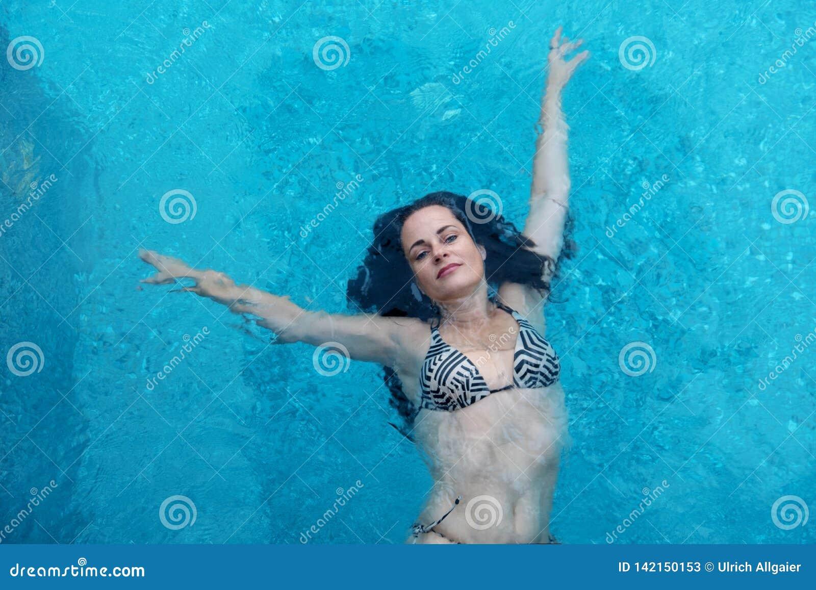 A mulher madura bonita em sua melhor idade com cabelo encaracolado escuro em nadadas do biquini com braços aumentou feliz elegant