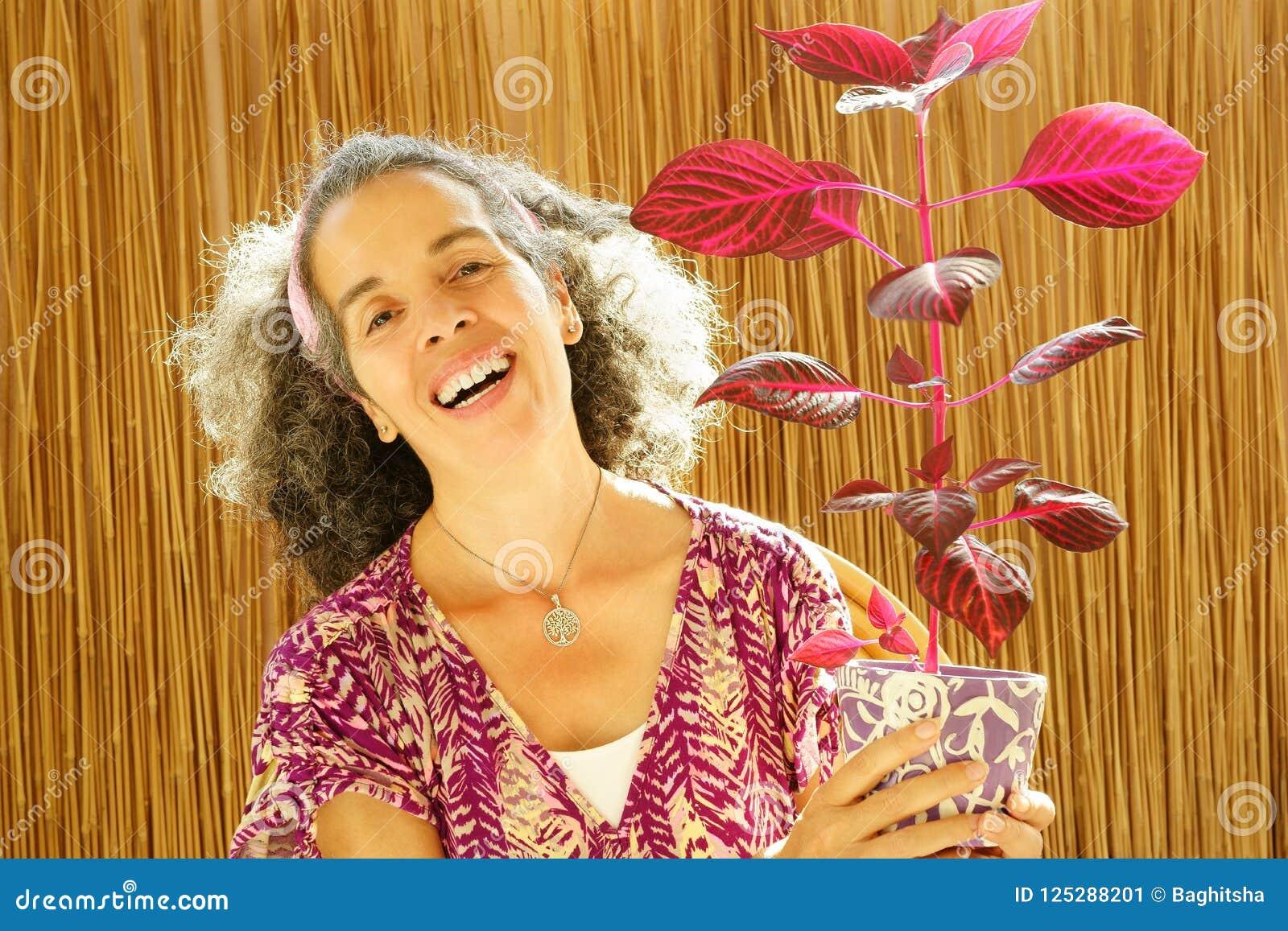 Mulher madura de riso natural que guarda a planta vermelha