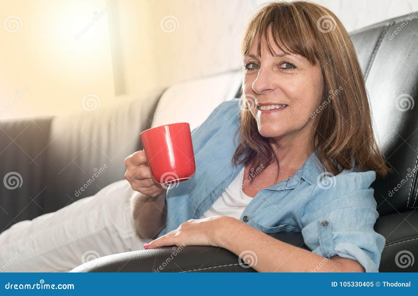 Mulher madura durante a ruptura de café em casa, efeito da luz