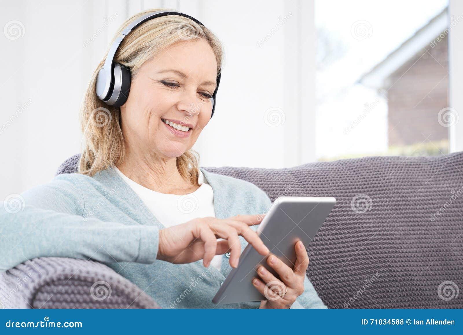 A mulher madura flui a música da tabuleta de Digitas a Headp sem fio