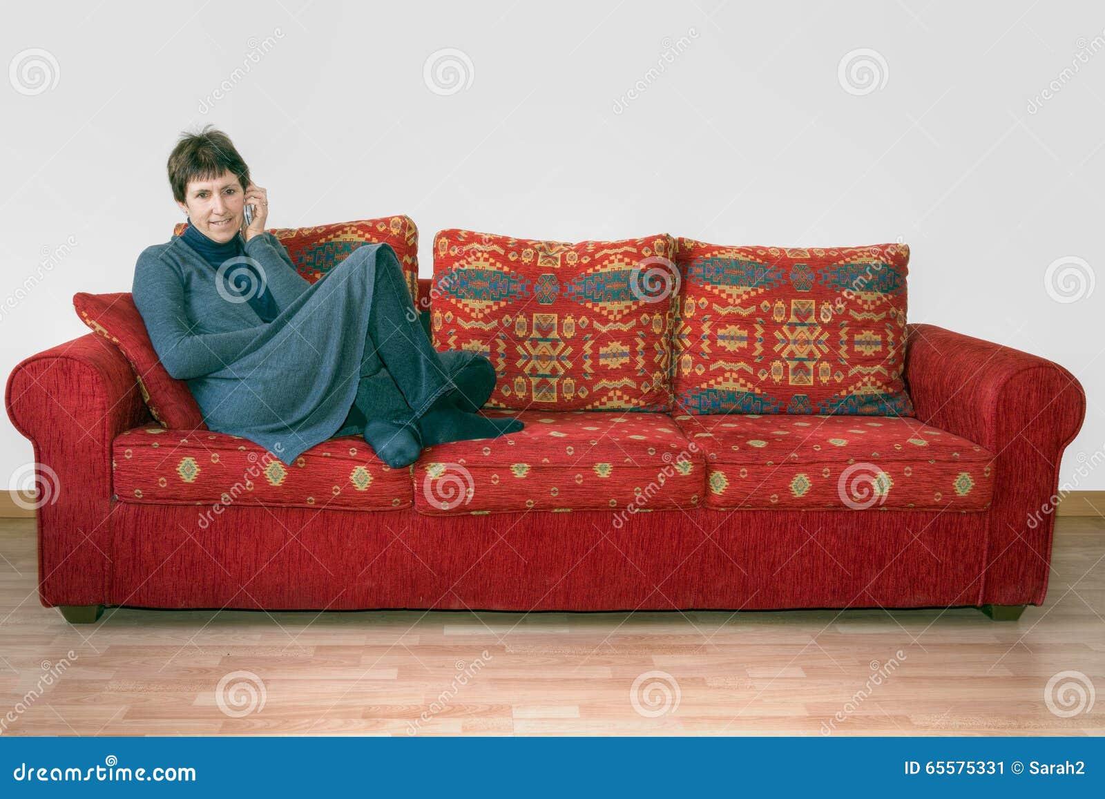 Mulher madura no sofá, canapé com telefone celular Conversa, bisbolhetice