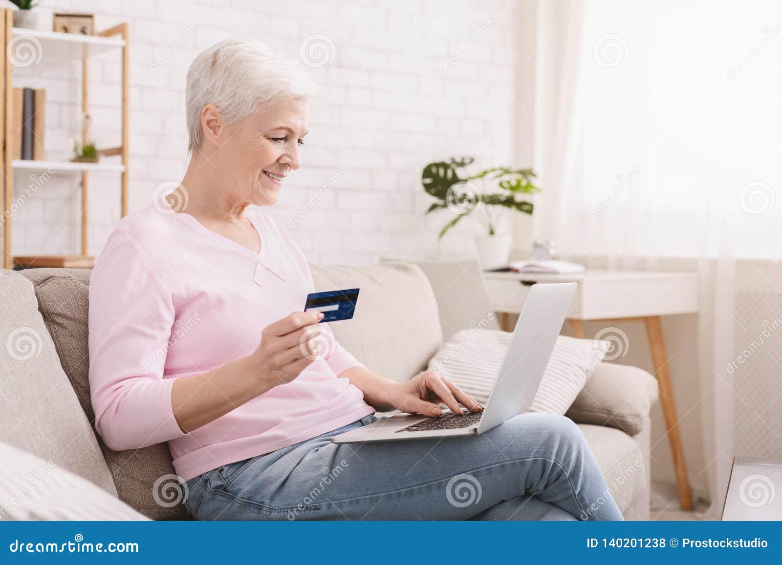 Mulher madura que compra em linha com cartão e portátil de crédito