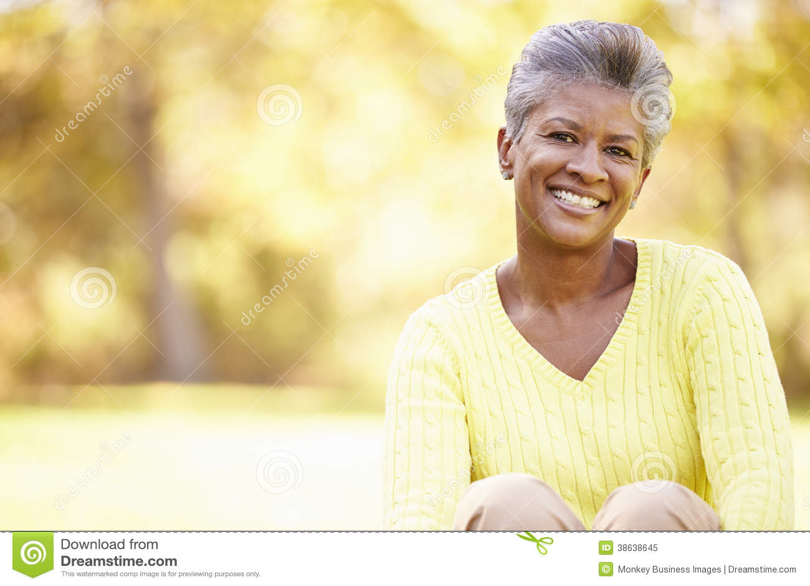 Mulher madura que relaxa em Autumn Landscape