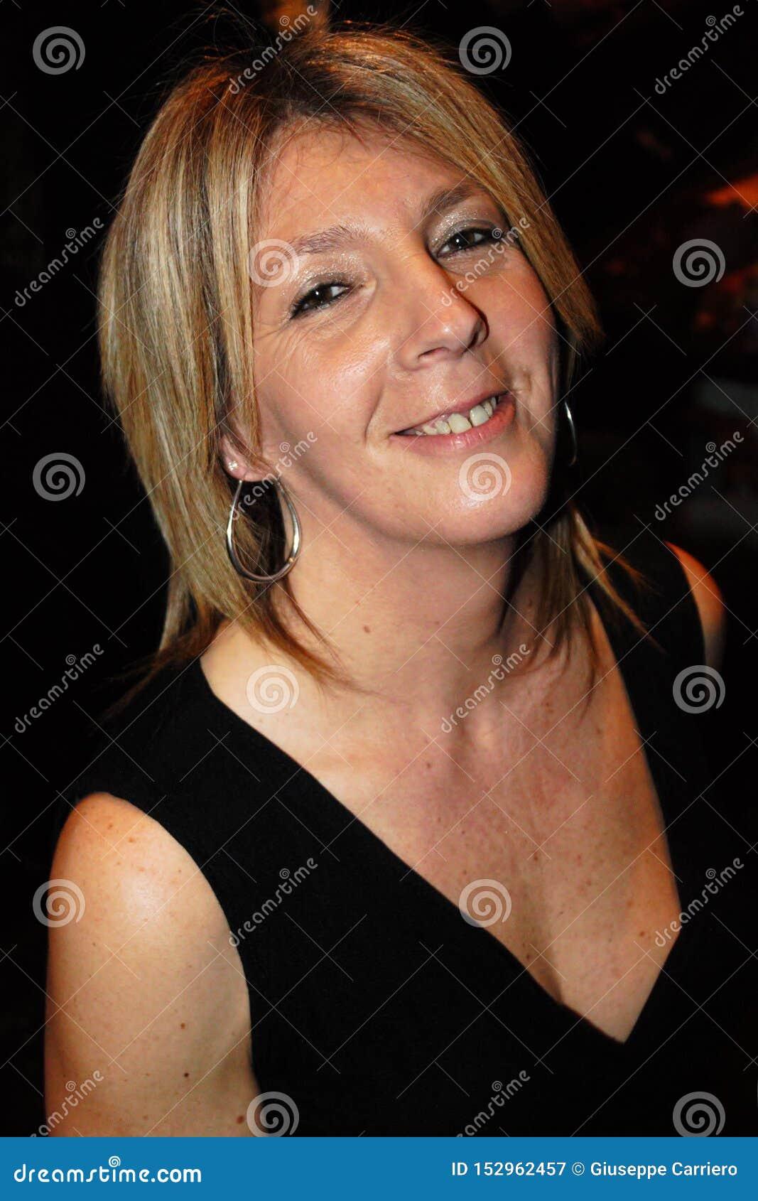 Mulher madura que sorri e sereno com vestido preto foto do busto