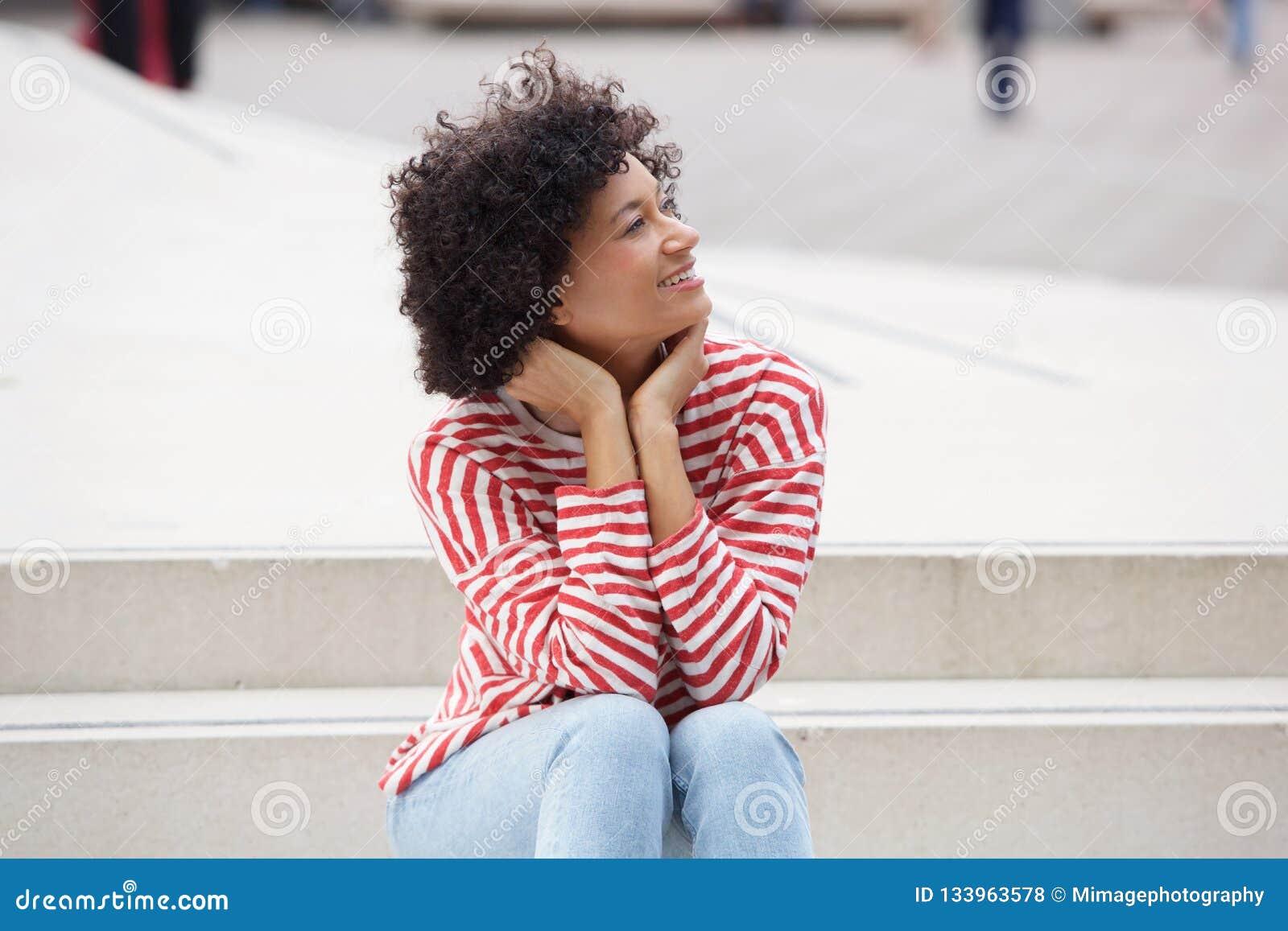 Mulher mais idosa atrativa que senta-se fora em etapas