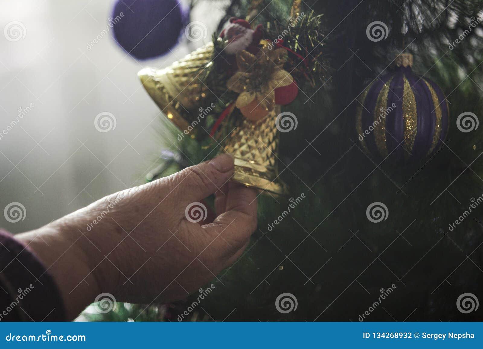 Mulher mais idosa que decora a árvore de Natal
