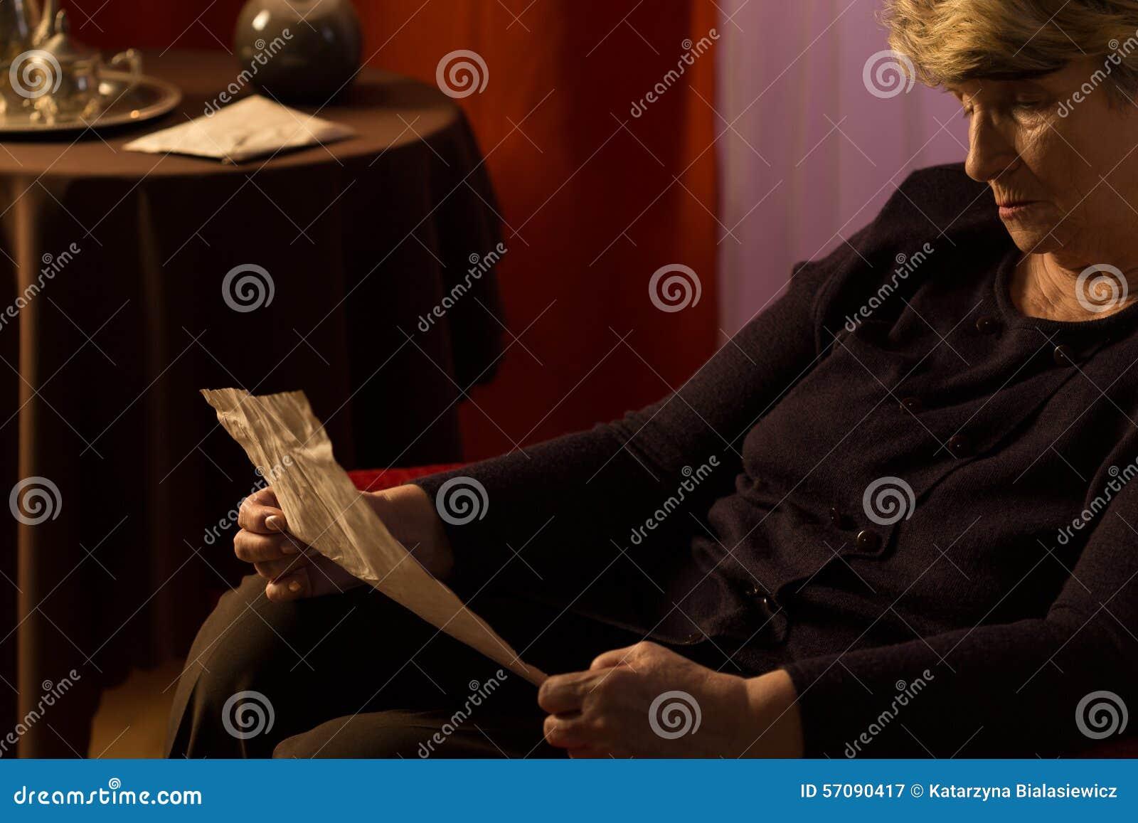 Mulher mais idosa que lê uma letra