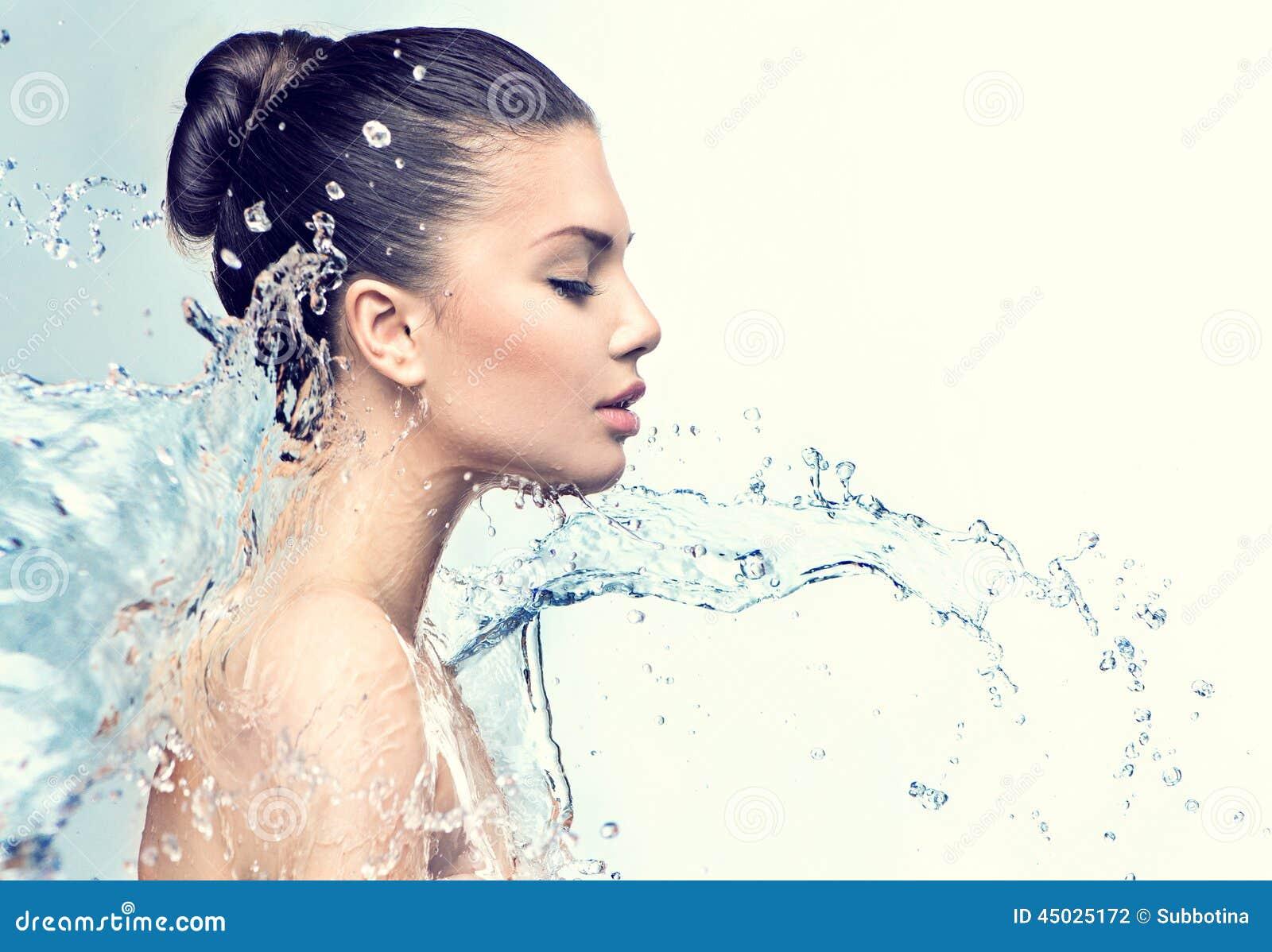 A mulher modelo bonita com espirra da água