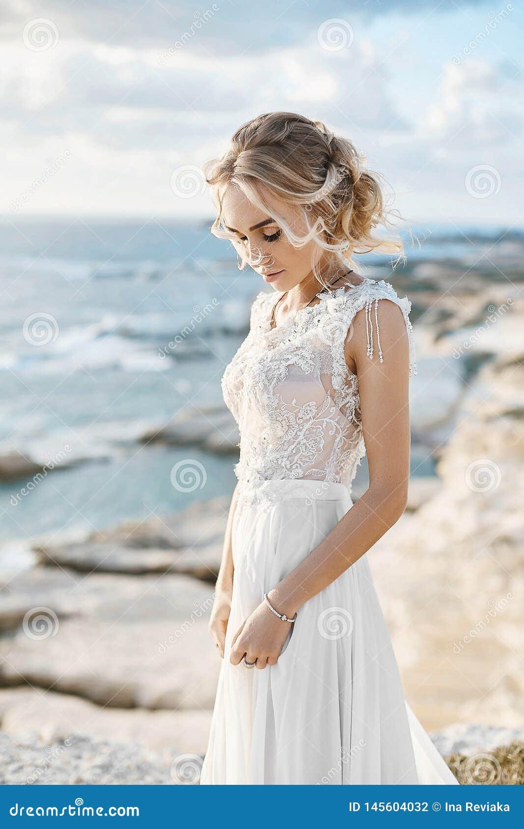 Mulher modelo loura nova bonita com composi??o nude em um vestido de casamento elegante que anda na costa de mar em Chipre