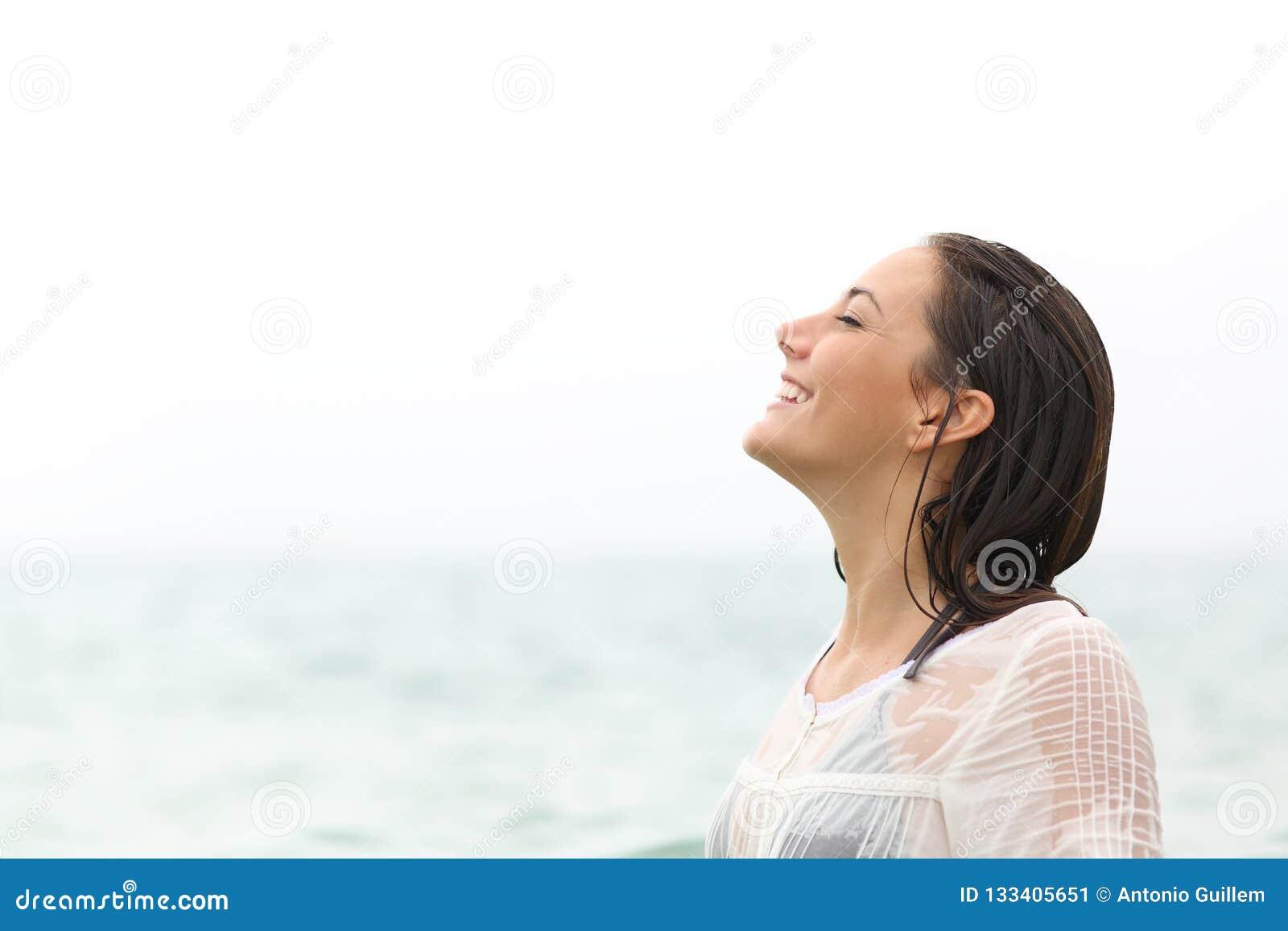 Mulher molhada que respira o ar fresco na praia