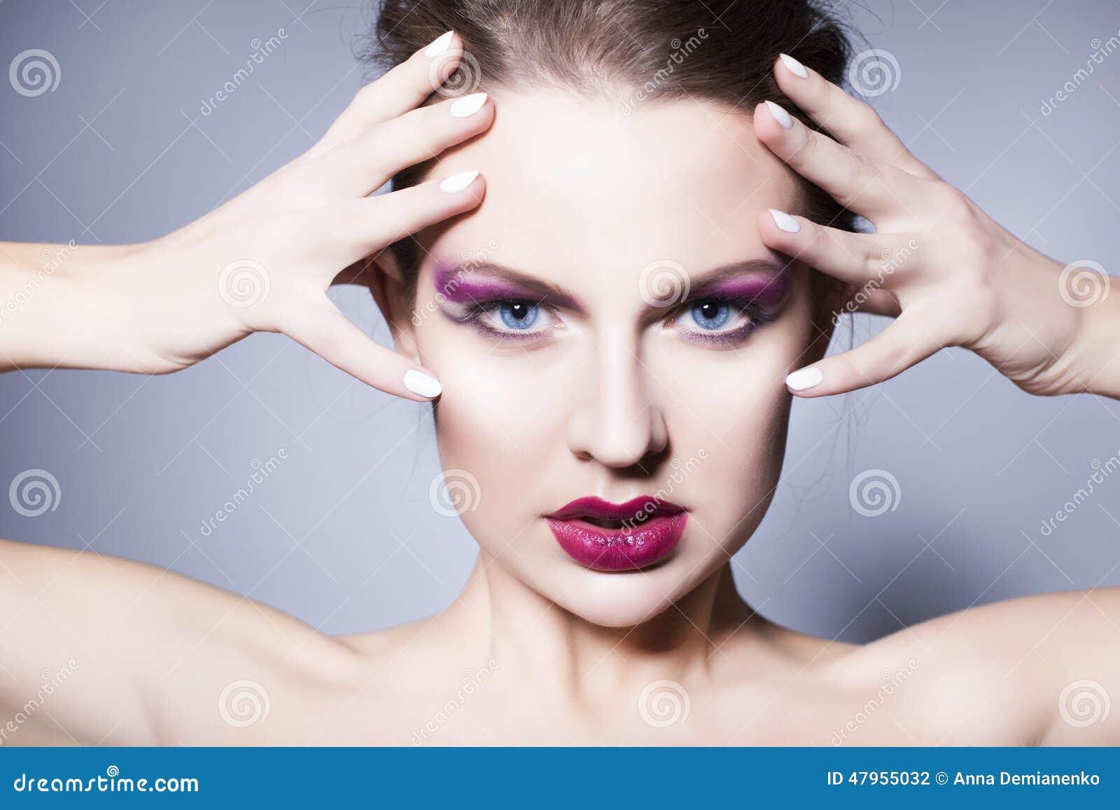 A mulher moreno com criativo compõe os bordos vermelhos completos das sombras para os olhos violetas, os olhos azuis e o cabelo e