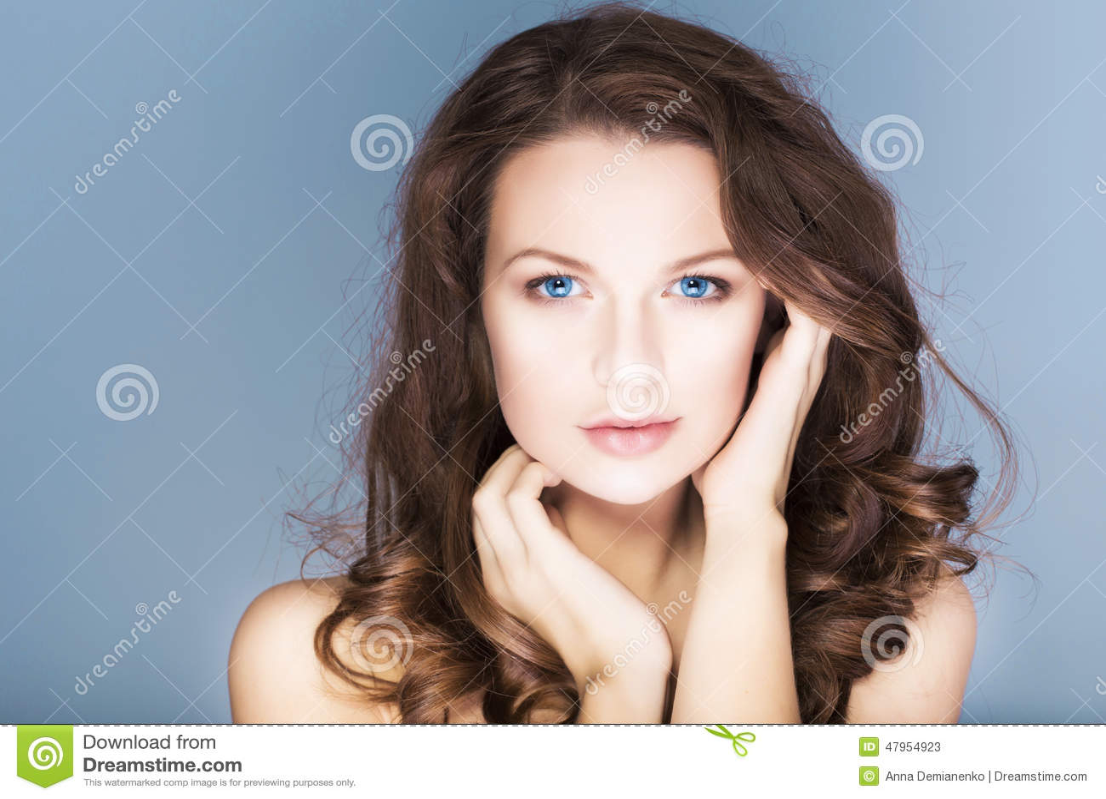 A mulher moreno com olhos azuis sem compõe, pele e as mãos sem falhas naturais perto de sua cara