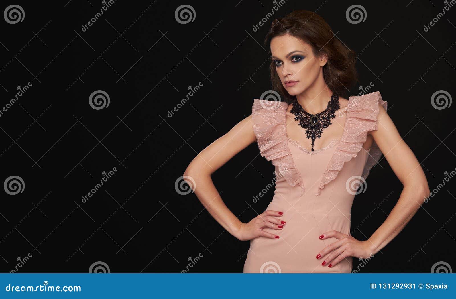 Mulher moreno elegante sobre o fundo preto
