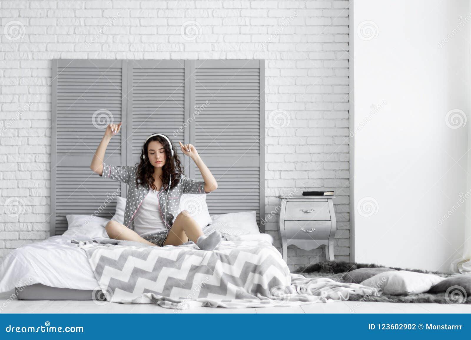 A mulher moreno engraçada feliz veste pijamas que escuta a música