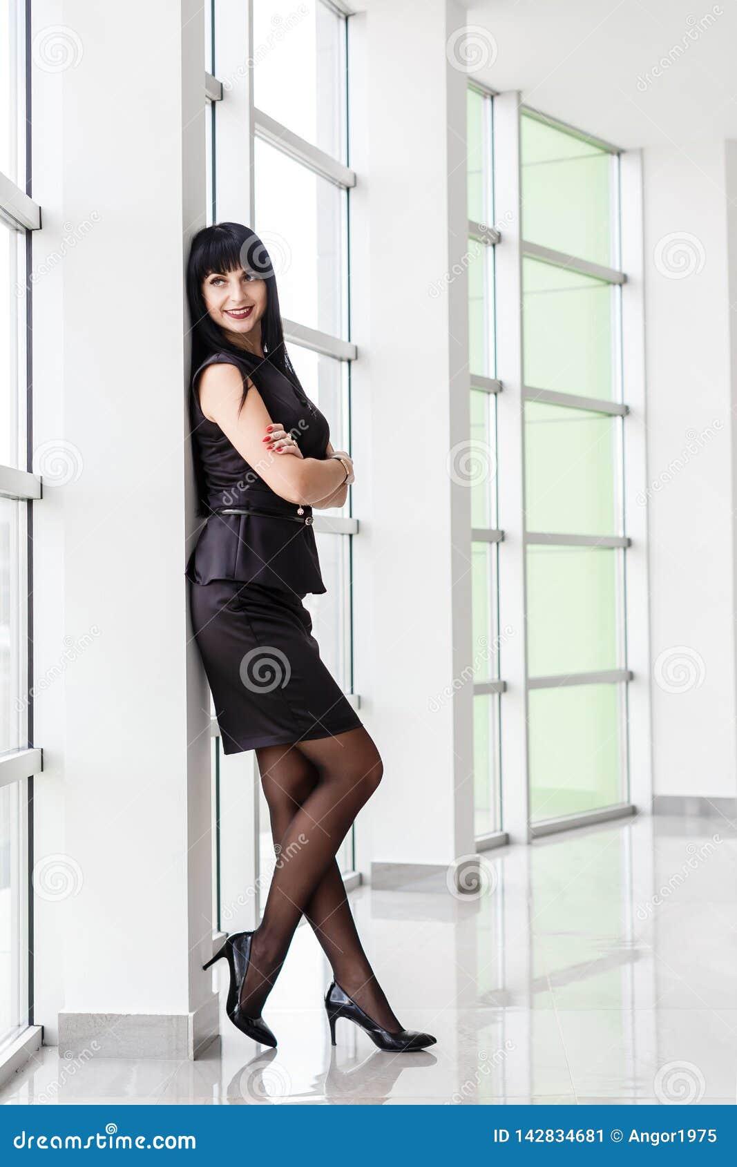 A mulher moreno feliz atrativa nova vestida em um terno de negócio preto com uma saia curto está estando perto da janela em um br