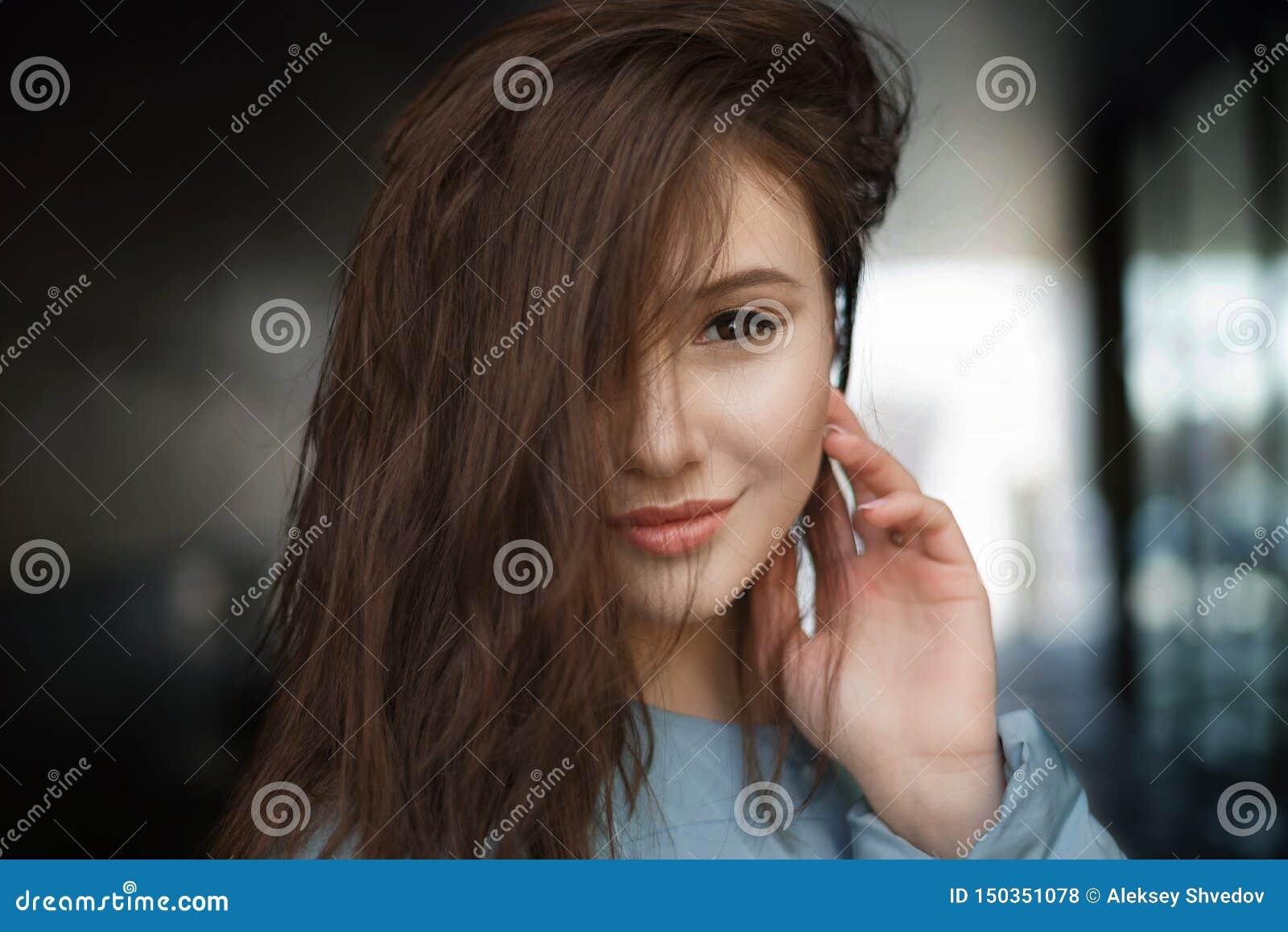 Mulher moreno feliz bonita que sorri na rua