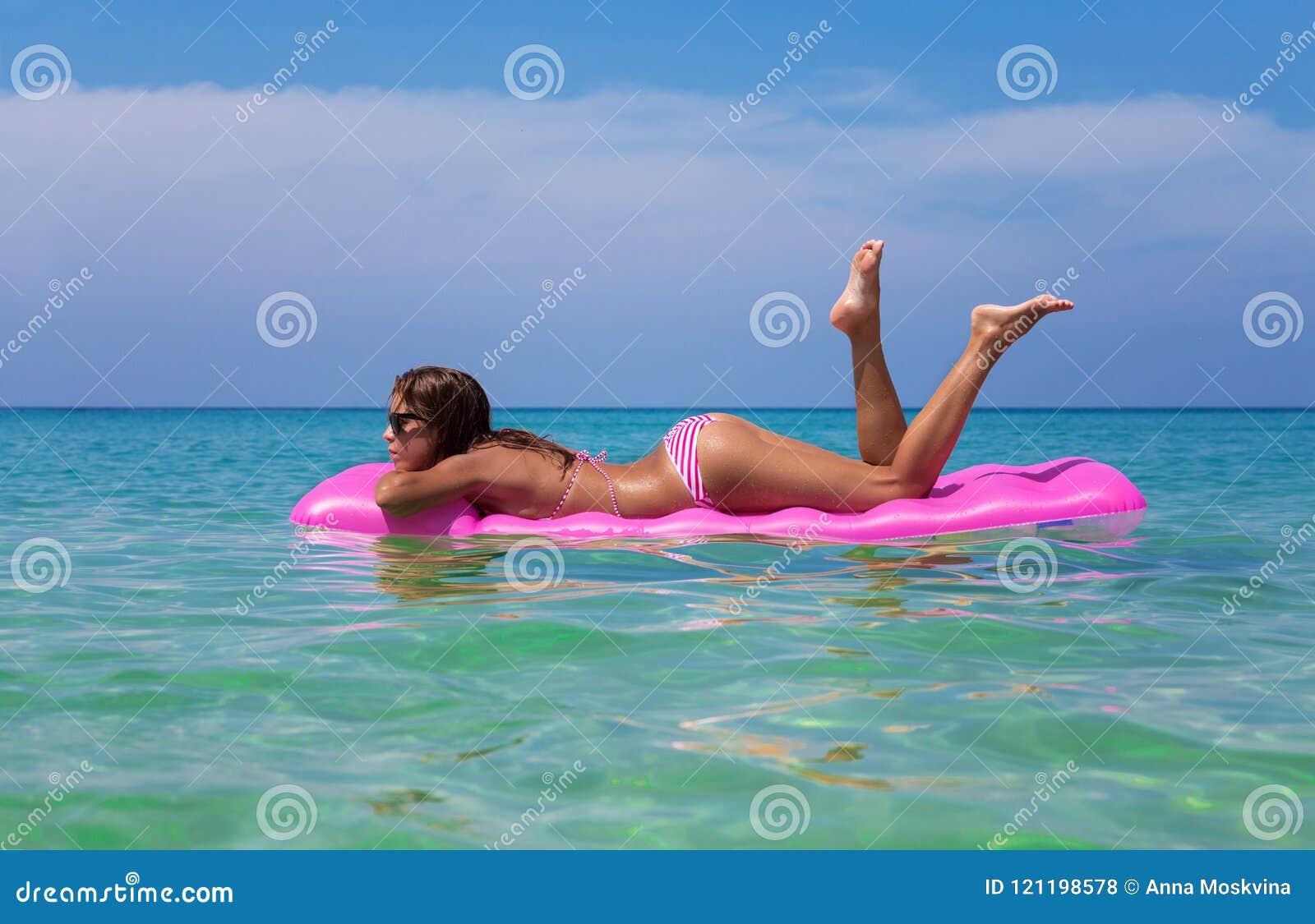Mulher moreno magro nova nos óculos de sol que nada em um mattr do ar