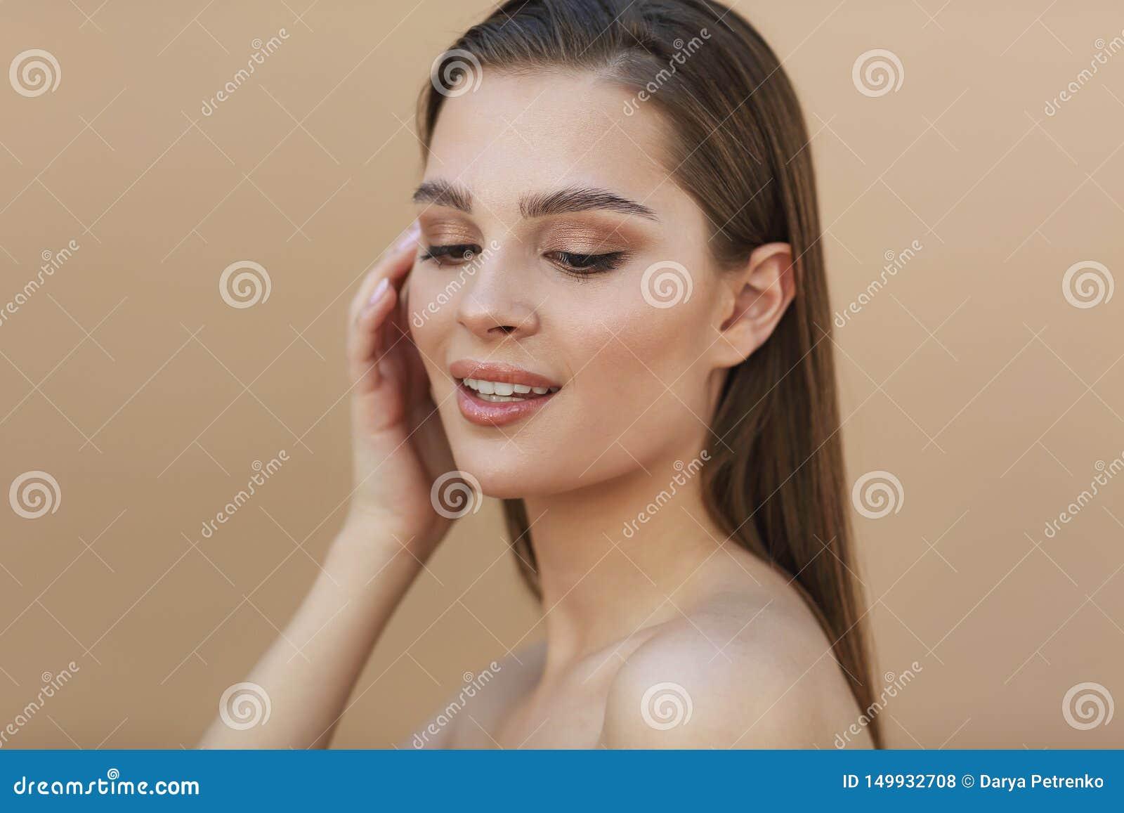 Mulher moreno nova bonita com a pele fresca limpa que toca em pr?prio cabelo