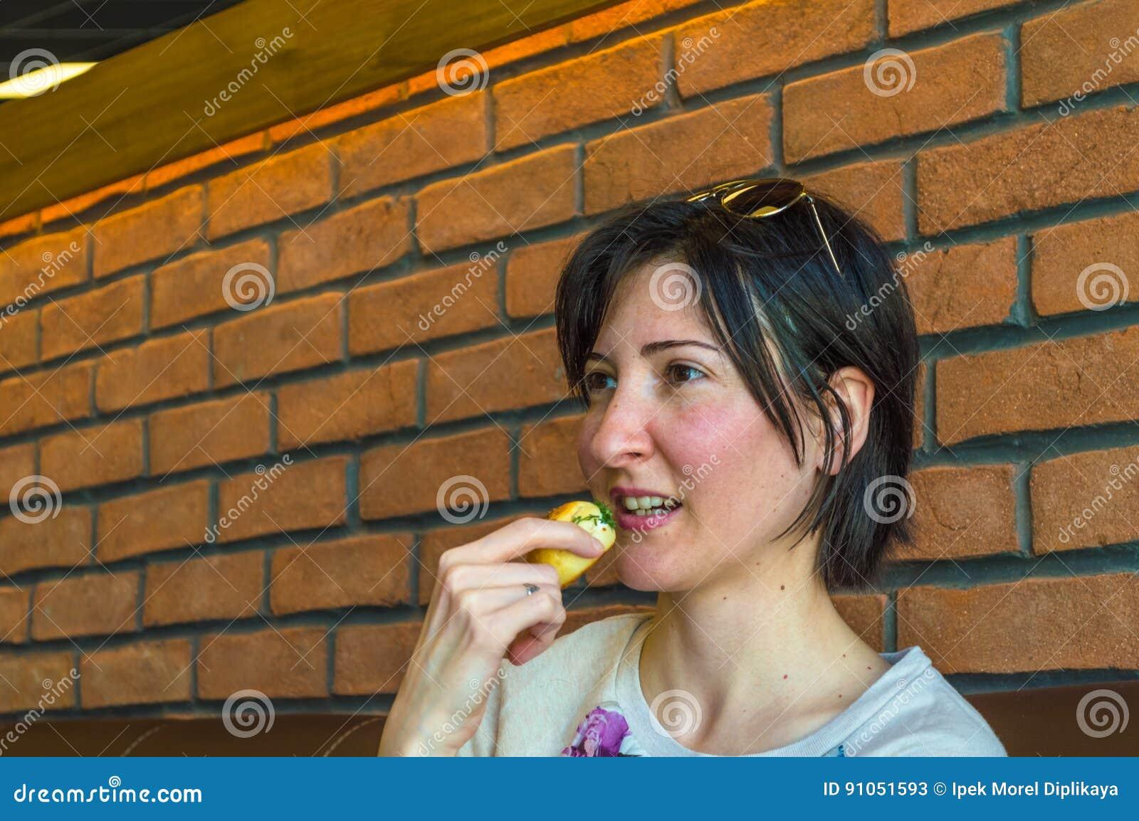 Mulher moreno nova com cabelo curto que come alguma pastelaria