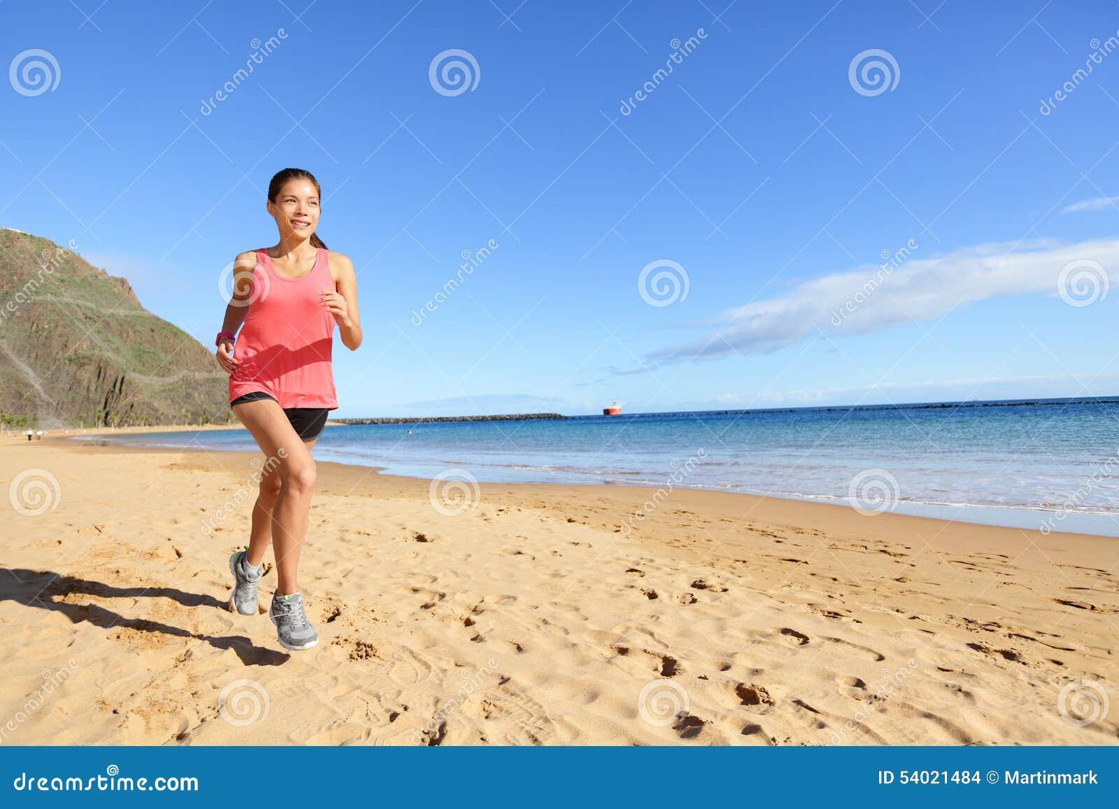 Mulher movimentando-se do corredor do atleta dos esportes na praia