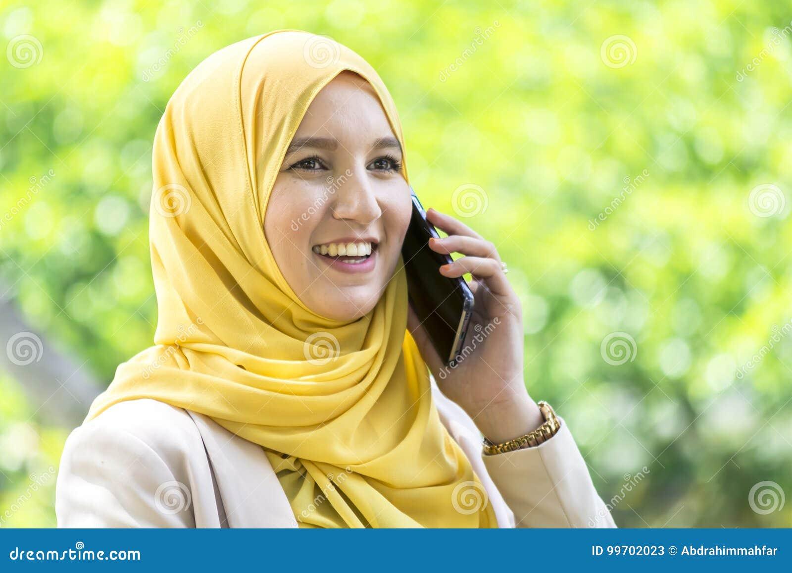 Mulher muçulmana consideravelmente nova que tem uma conversação no telefone