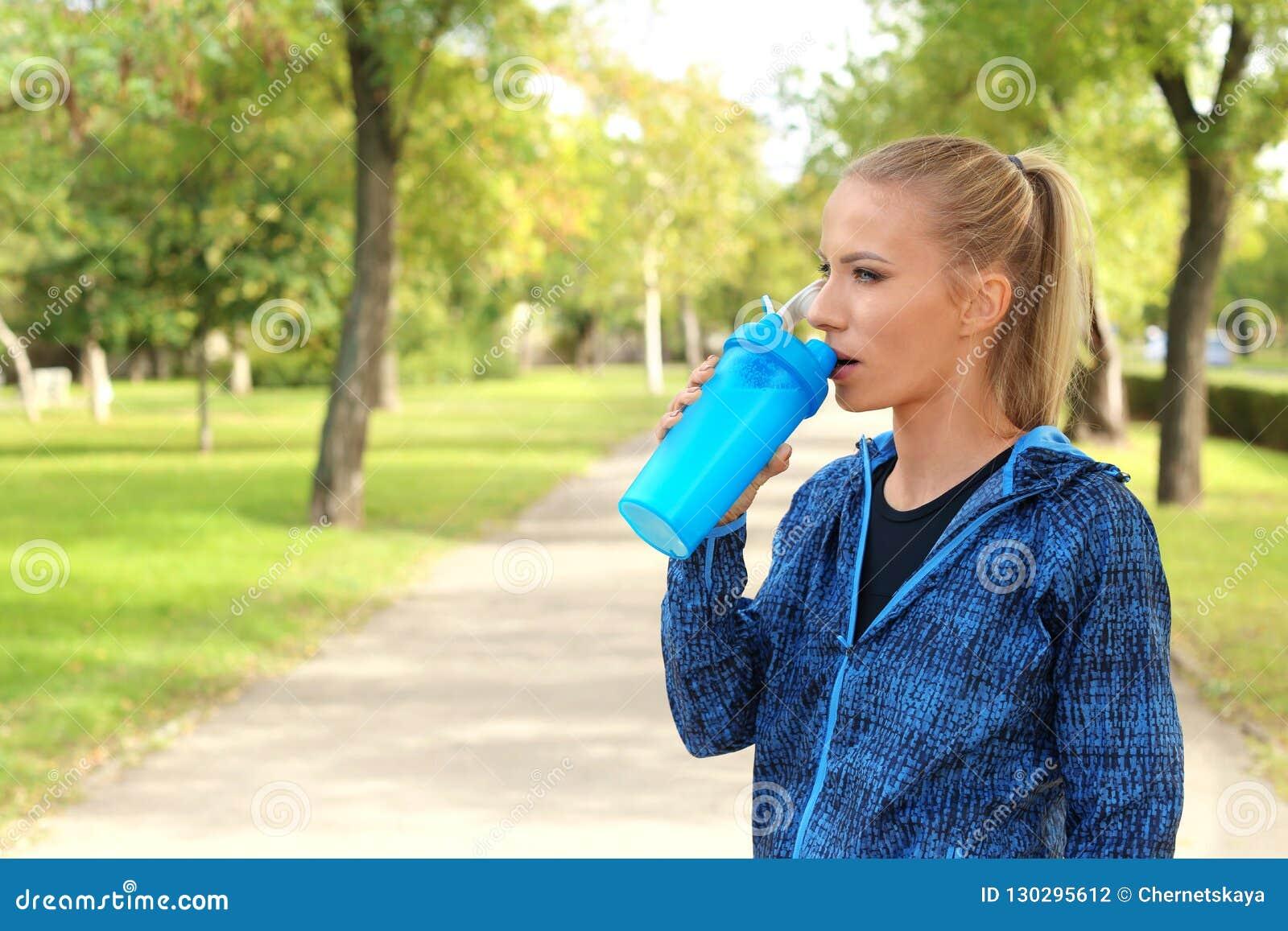 Mulher na agitação bebendo da proteína do sportswear