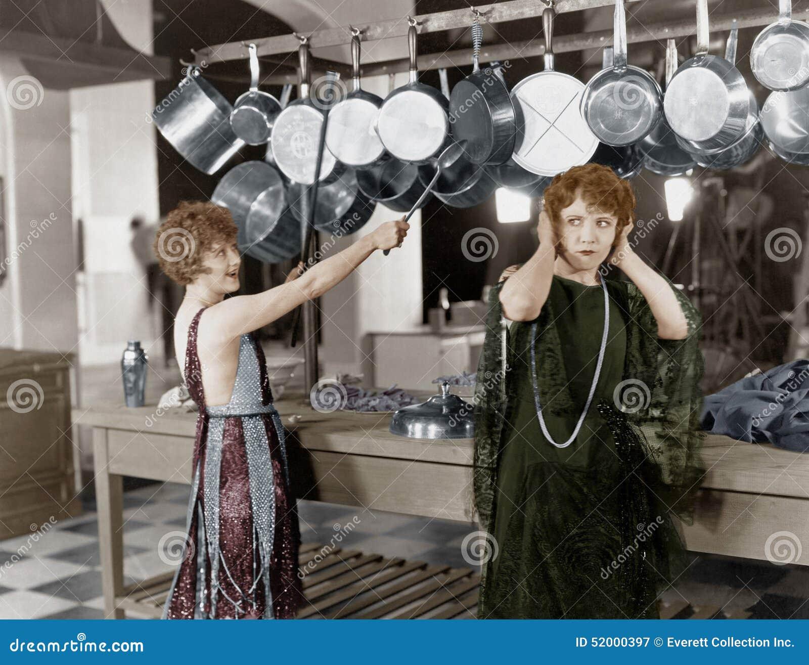 Mulher na batida da cozinha em potenciômetros e bandejas (todas as pessoas descritas não são umas vivas mais longo e nenhuma prop