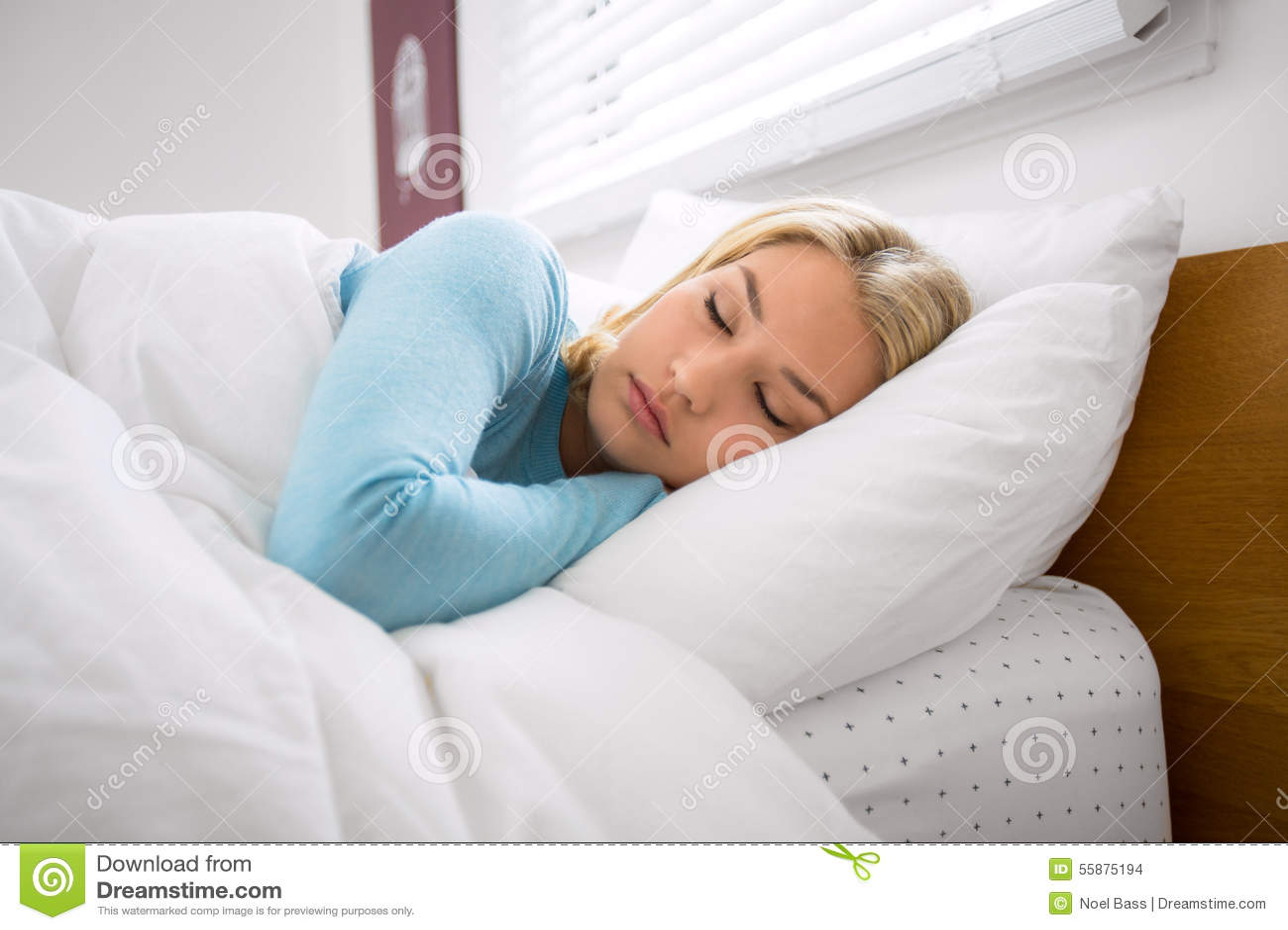 Mulher na cama com descanso fechado dos olhos pacificamente e sono tomando uma sesta