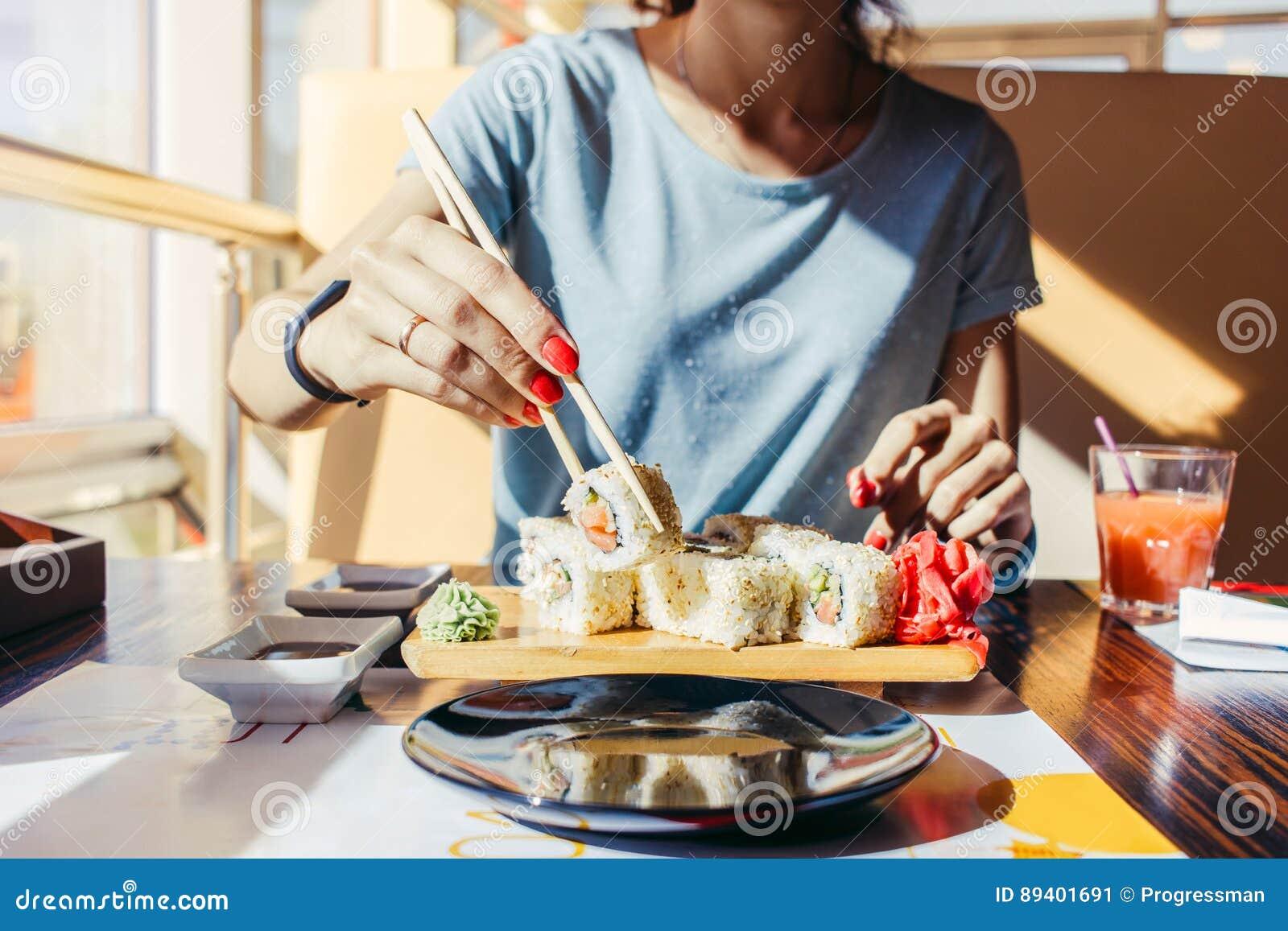 A mulher na camisa azul está comendo em um restaurante de sushi no summe