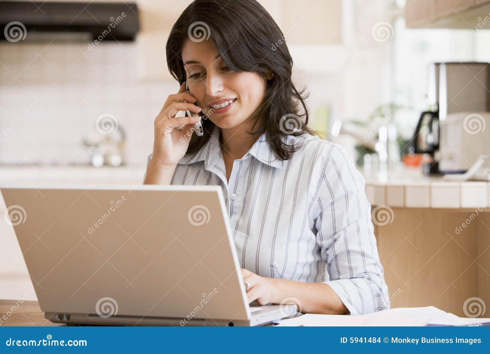 Mulher na cozinha com portátil usando o telemóvel